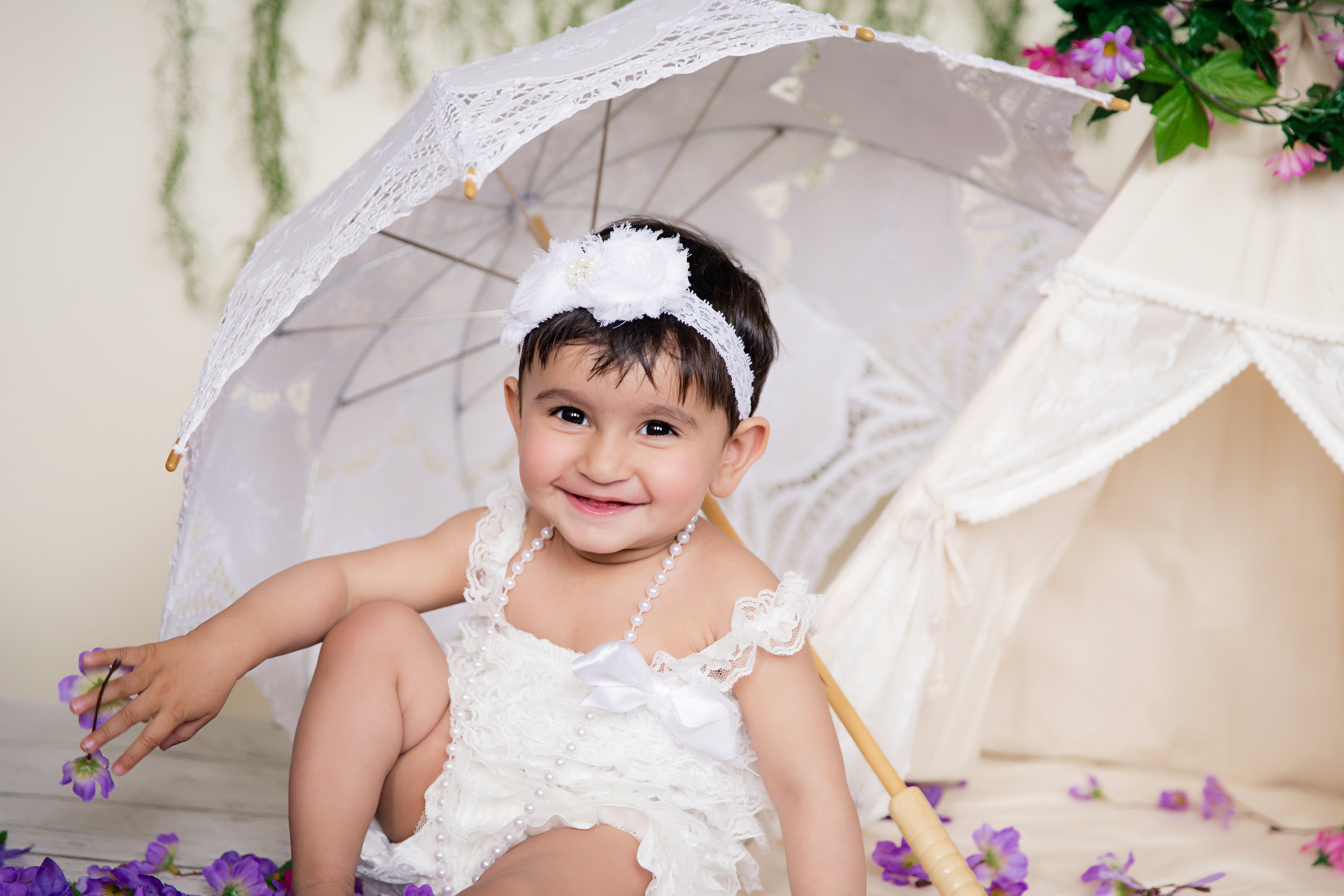 Baby girl wearing a white romper smiling.  Umbrella and tipi set up. 1st Birthday photoshoot ideas. Calgary Photographer. Milashka Photography