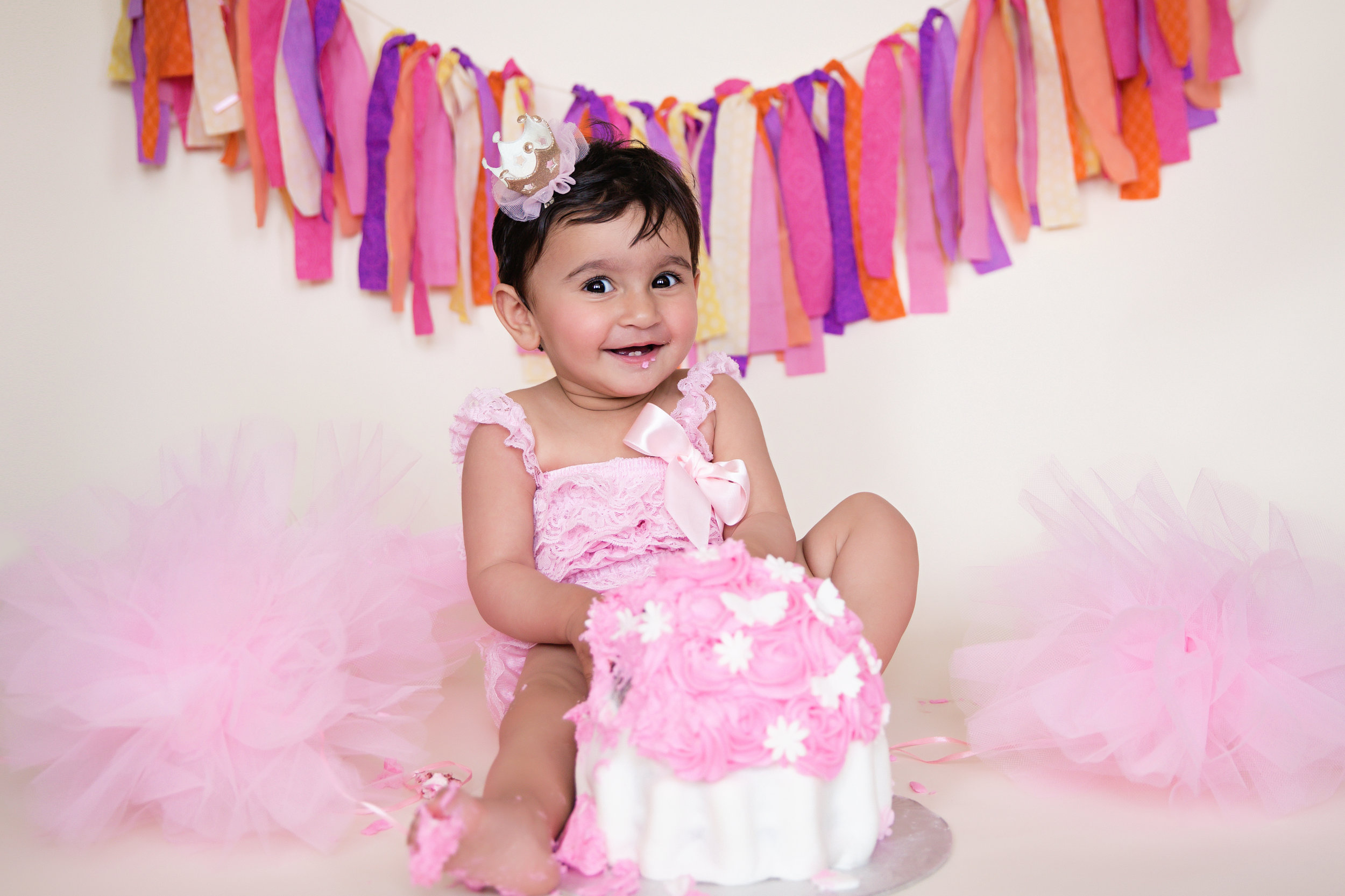 Cakesmash photoshoot. Baby girl wearing a pink romper smashing her cake. Calgary photographer. Milashka Photography