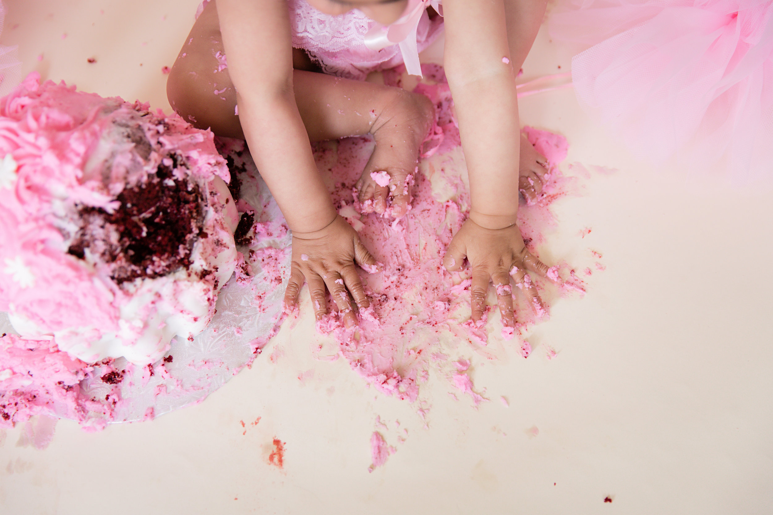 Little hands and feet covered in icing after a successful cakesmash. Calgary cakesmash photographer. Milashka Photography