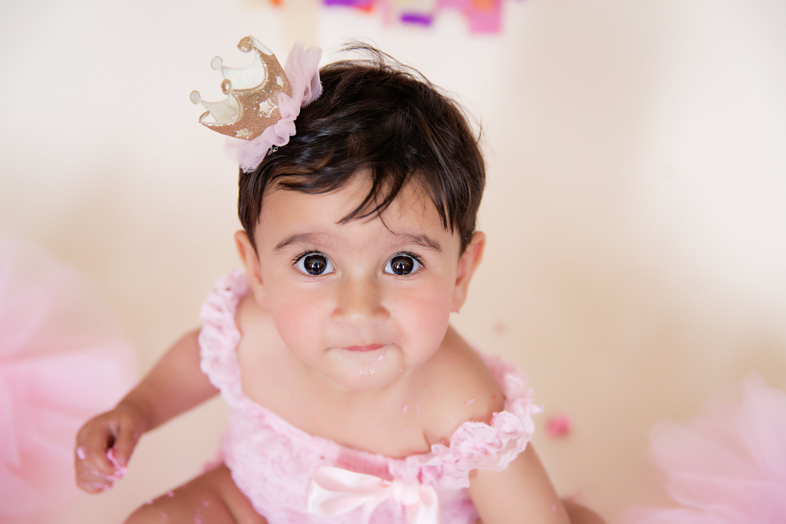 Baby with beautiful eyes looking straight at the camera. Cakesmash photoshoot. Calgary. Milashka Photography