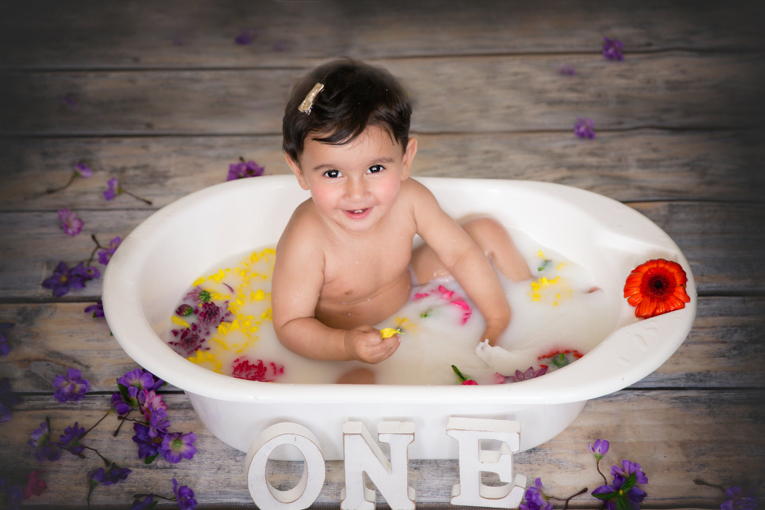 Milk bath for a one year old. Little girl sitting in a milk bath, surrounded by flowers and smiling. Milk bath photoshoot. Calgary photographer. Milashka Photography.