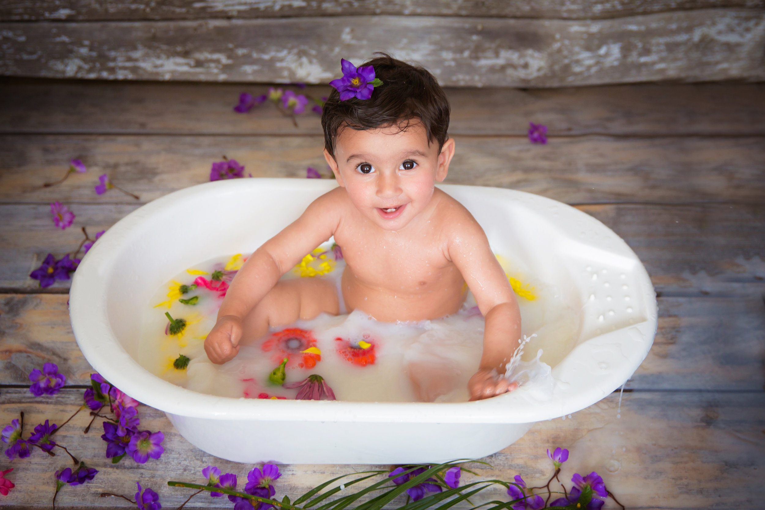 Milk bath photoshoot ideas for a one-year-old.  Little girl splashing in a milk bath, surrounded by flowers. Calgary milk bath photoshoot. Milashka Photography