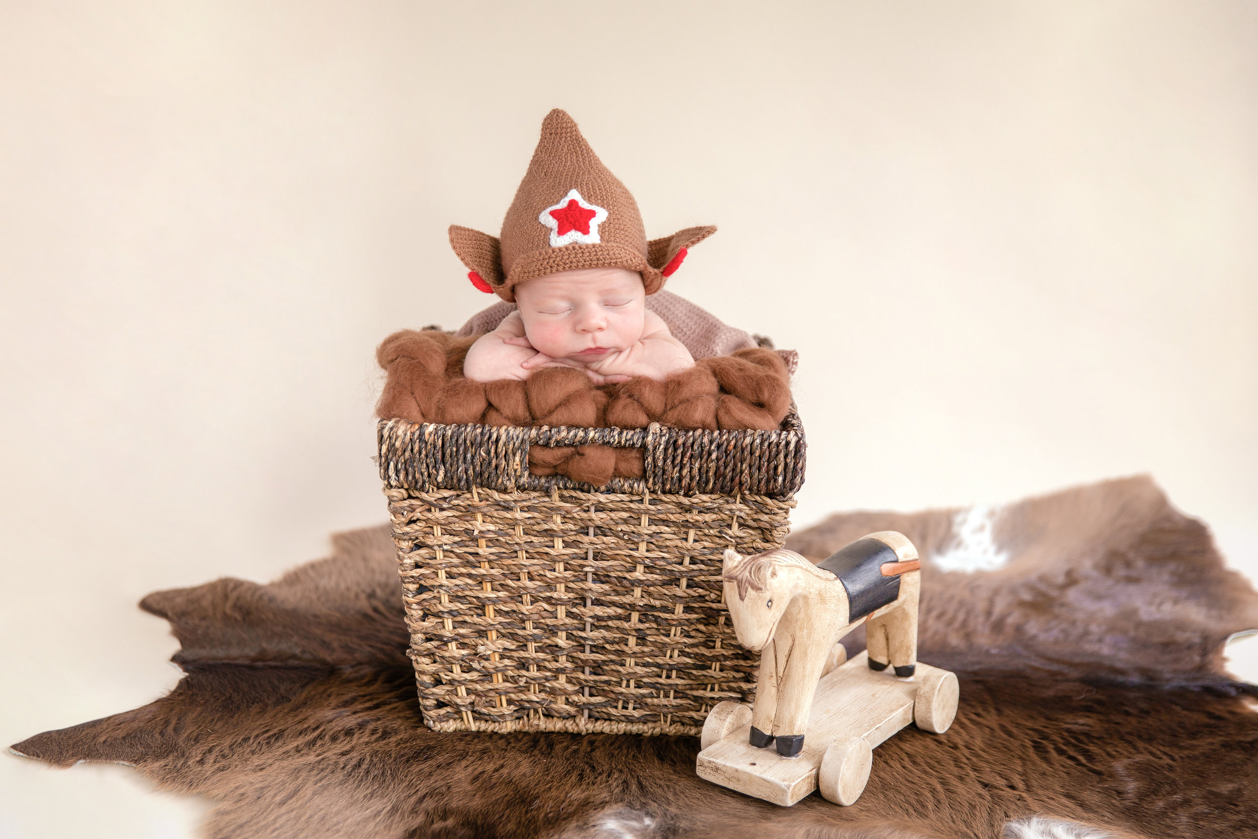 Russian Inspired Newborn Photoshoot. Baby boy in a basket wearing a Russian Civil War hat - budenovka with a wooden horse beside him. Calgary Newborn Photographer. Russian Newborn Photographer. Milashka Photography