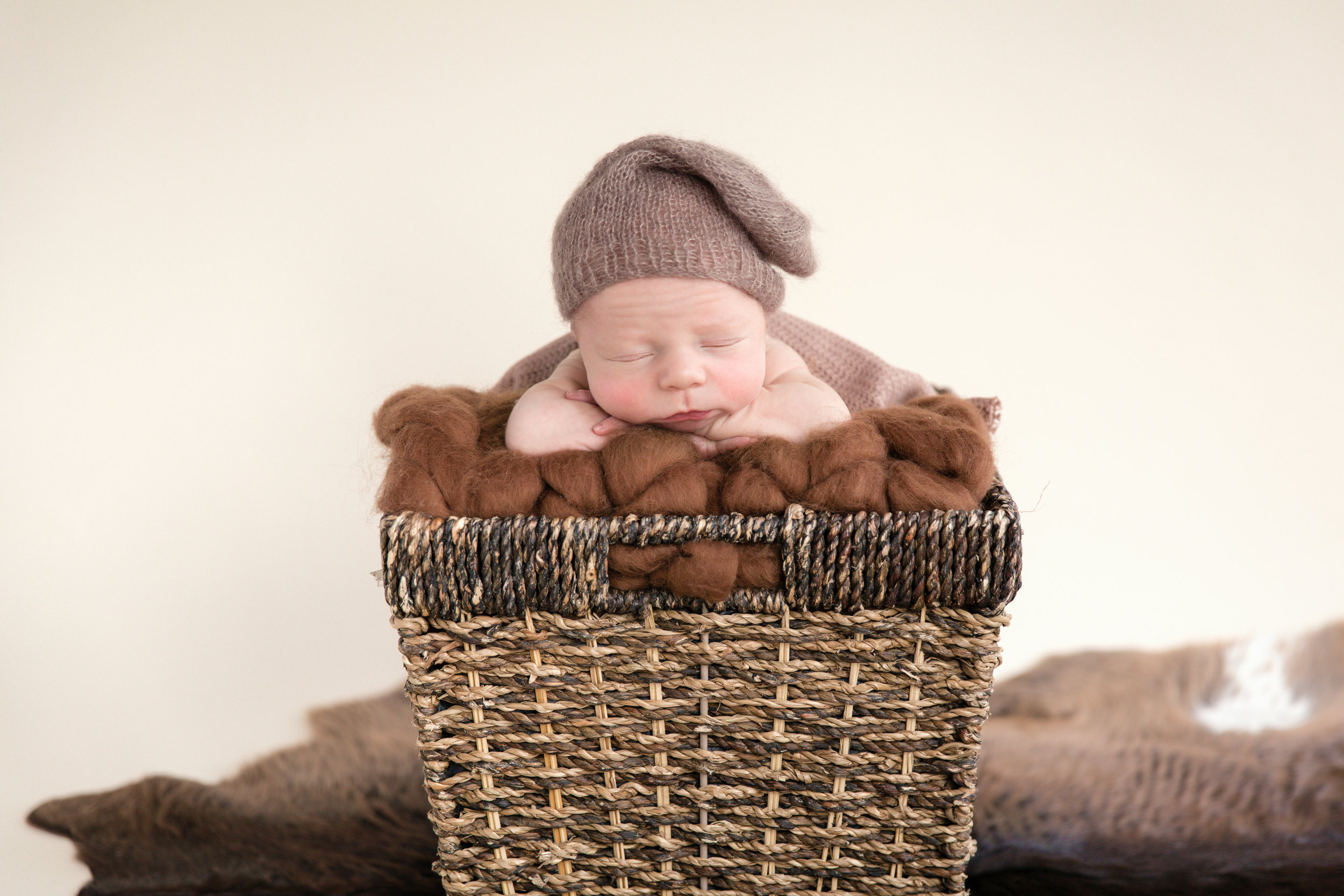 Newborn baby boy in a basket with a cute brown hat. Calgary Newborn photographer. Milashka Photography