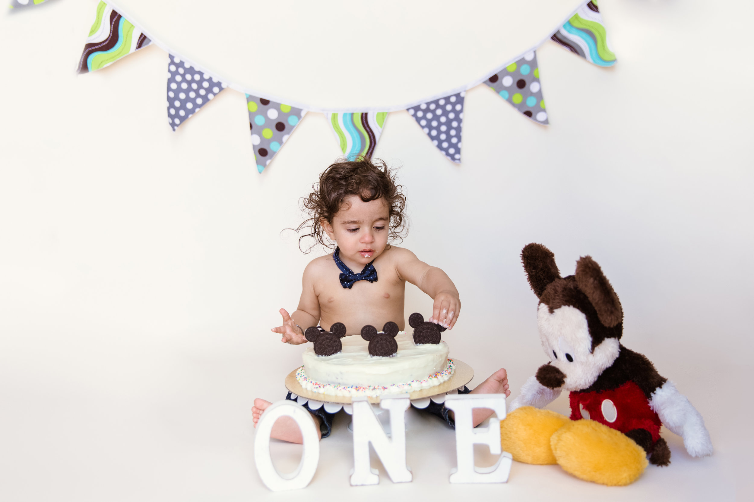 Mickey Mouse Inspired Cakesmash Photoshoot. Birthday Boy is about to taste his first bite of his birthday cake. Calgary Cakesmash Photographer. Milashka Photography