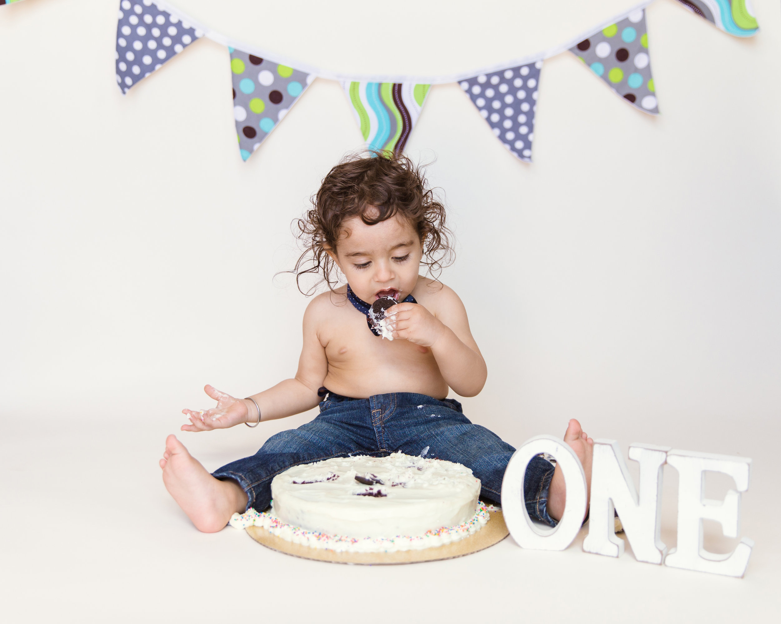 Birthday boy is enjoying his cake during his cakesmash photoshoot. Calgary cakesmash. Milashka Photography