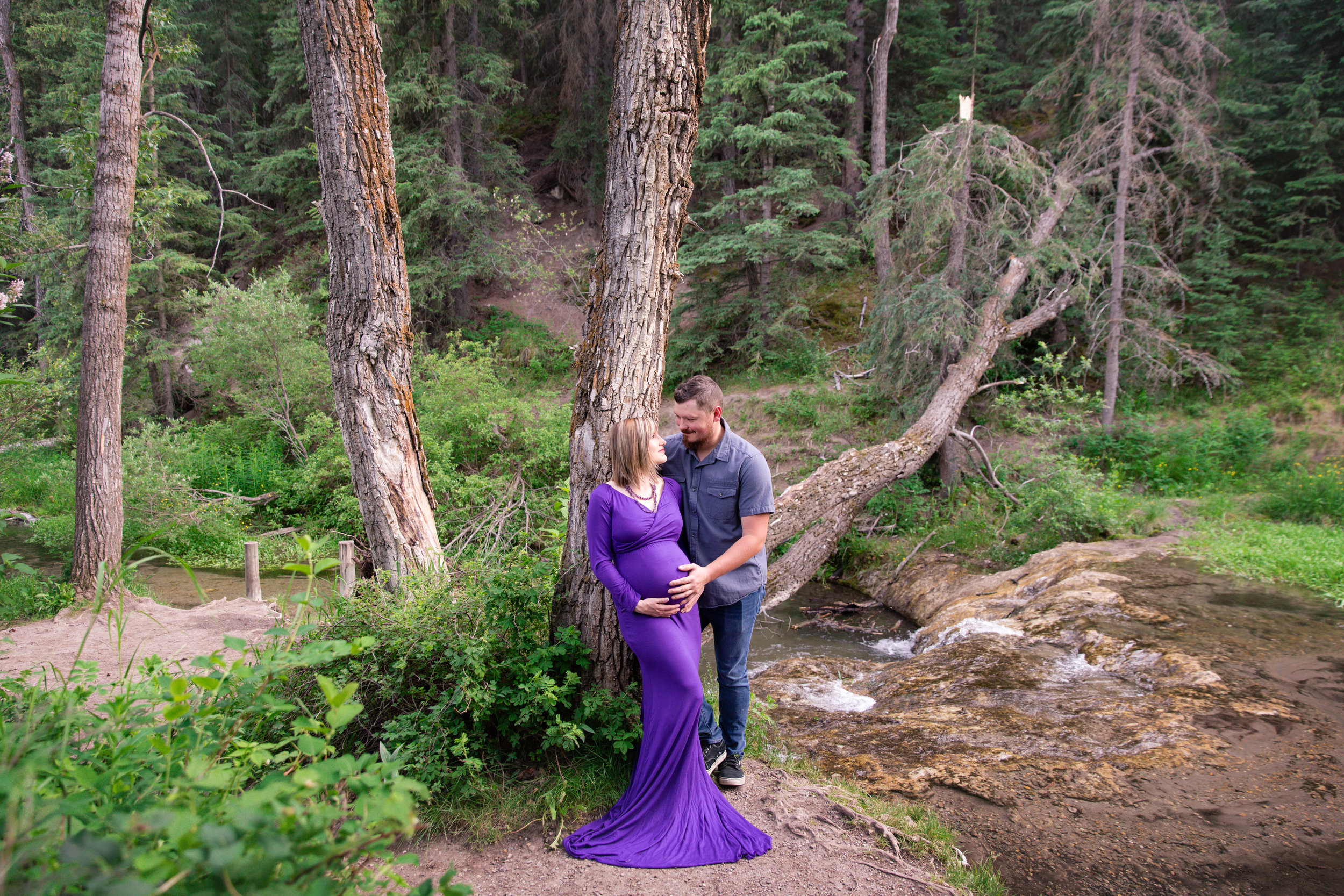 Expecting couple in a forest. Mom-to-be is wearing a beautiful purple gown.