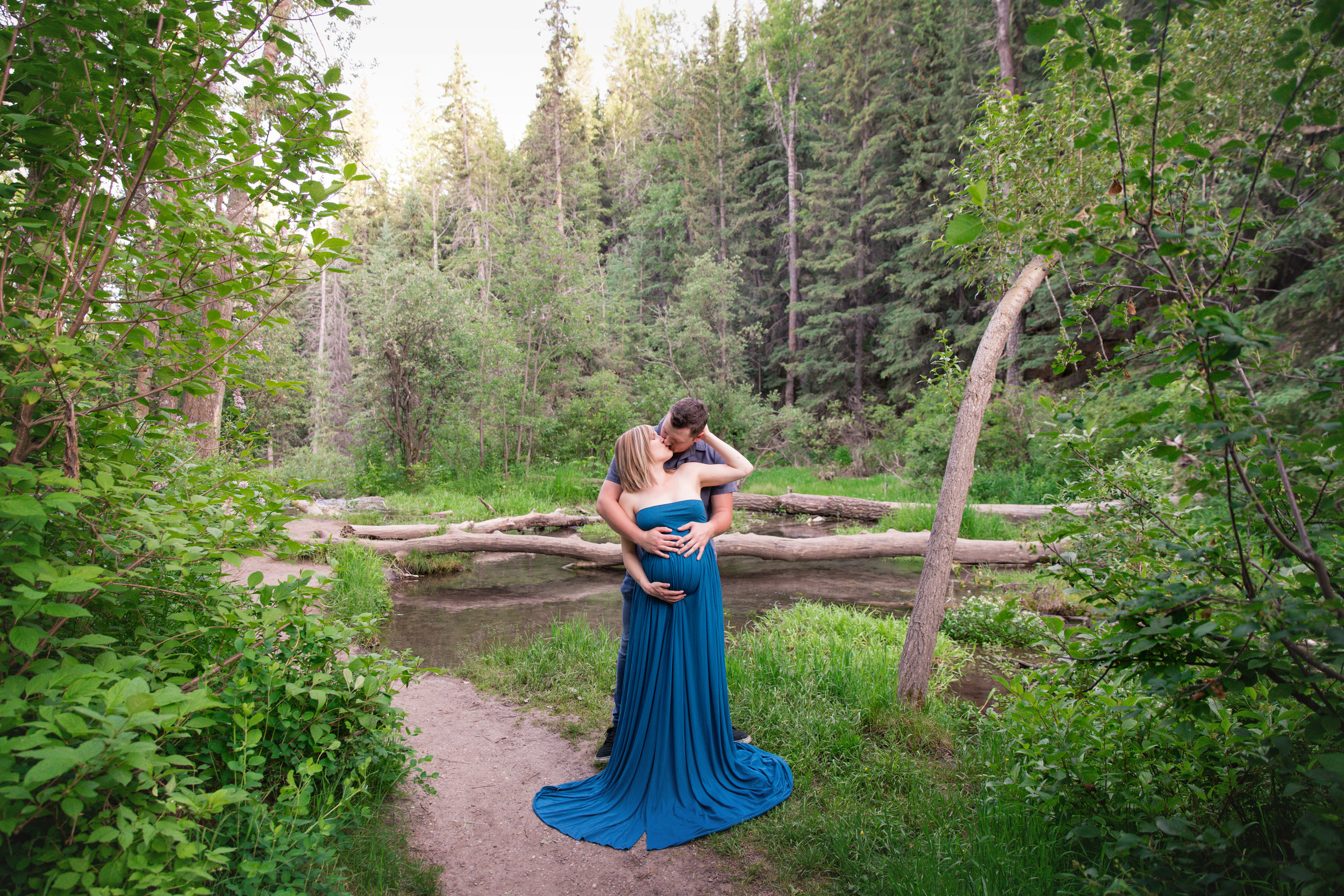 Expecting couple in a forest kissing. Mom-to-be is wearing a blue dress. Calgary Maternity Photographer. Milashka Photography