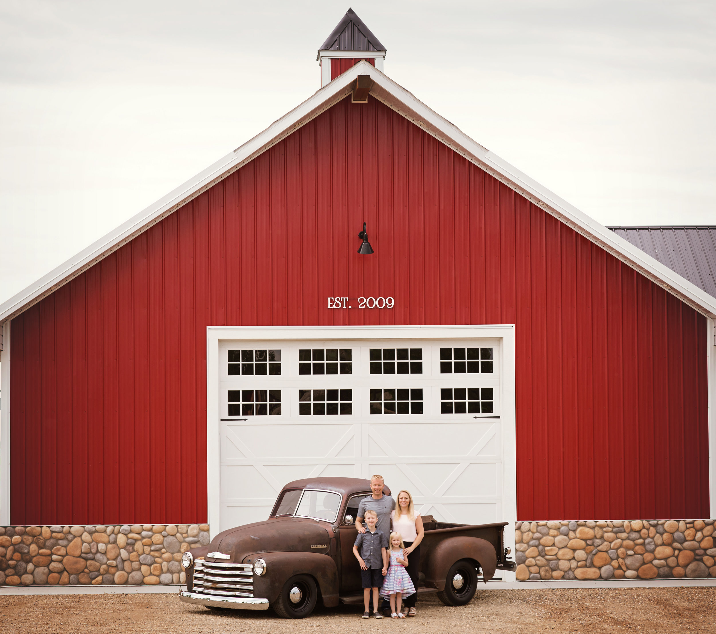Family of 4 standing in front of a big red barn and an old truck. Calgary family photographer. Milashka Photography