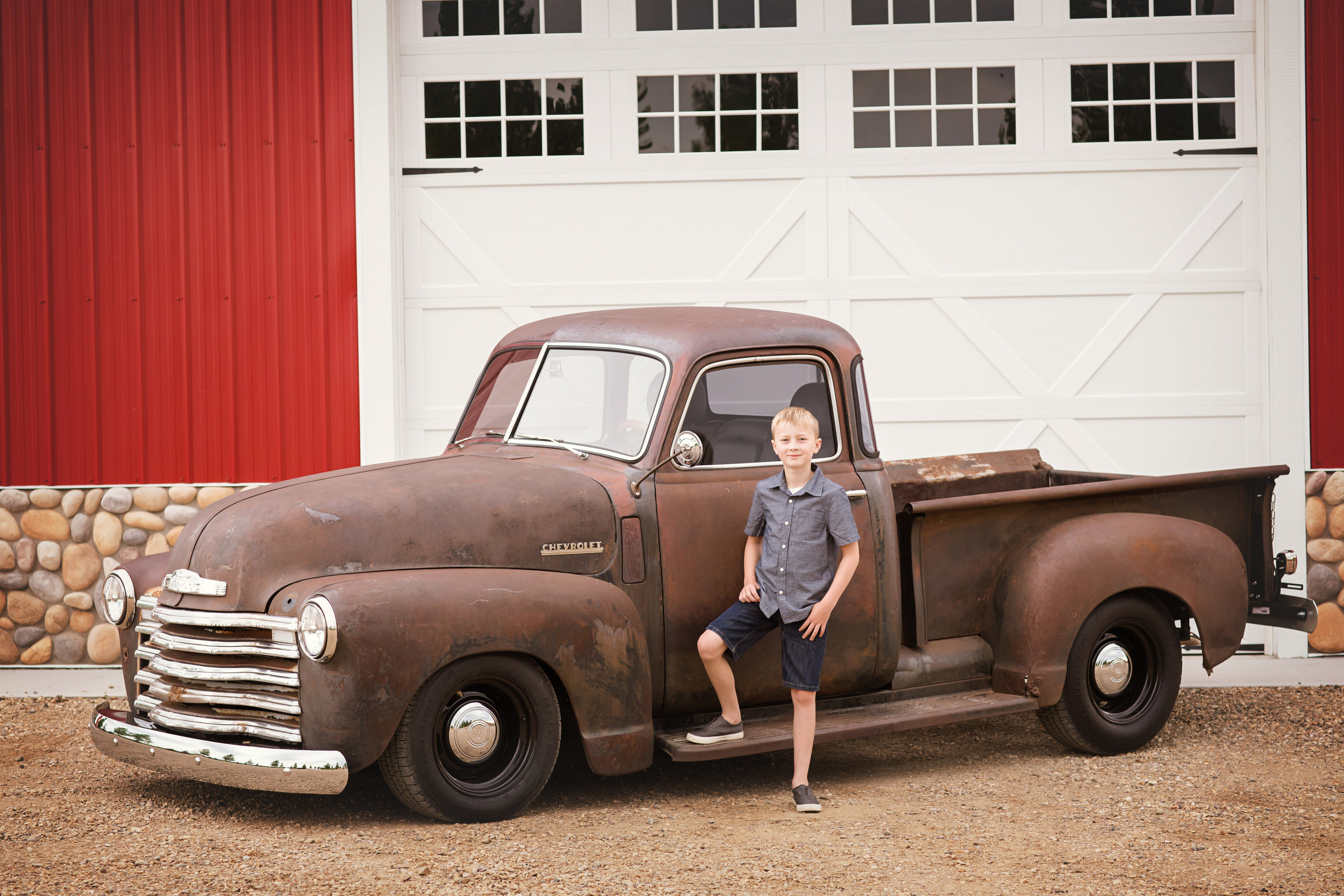 Boy standing beside an old truck and red barn. Calgary family photographer - Milashka Photography