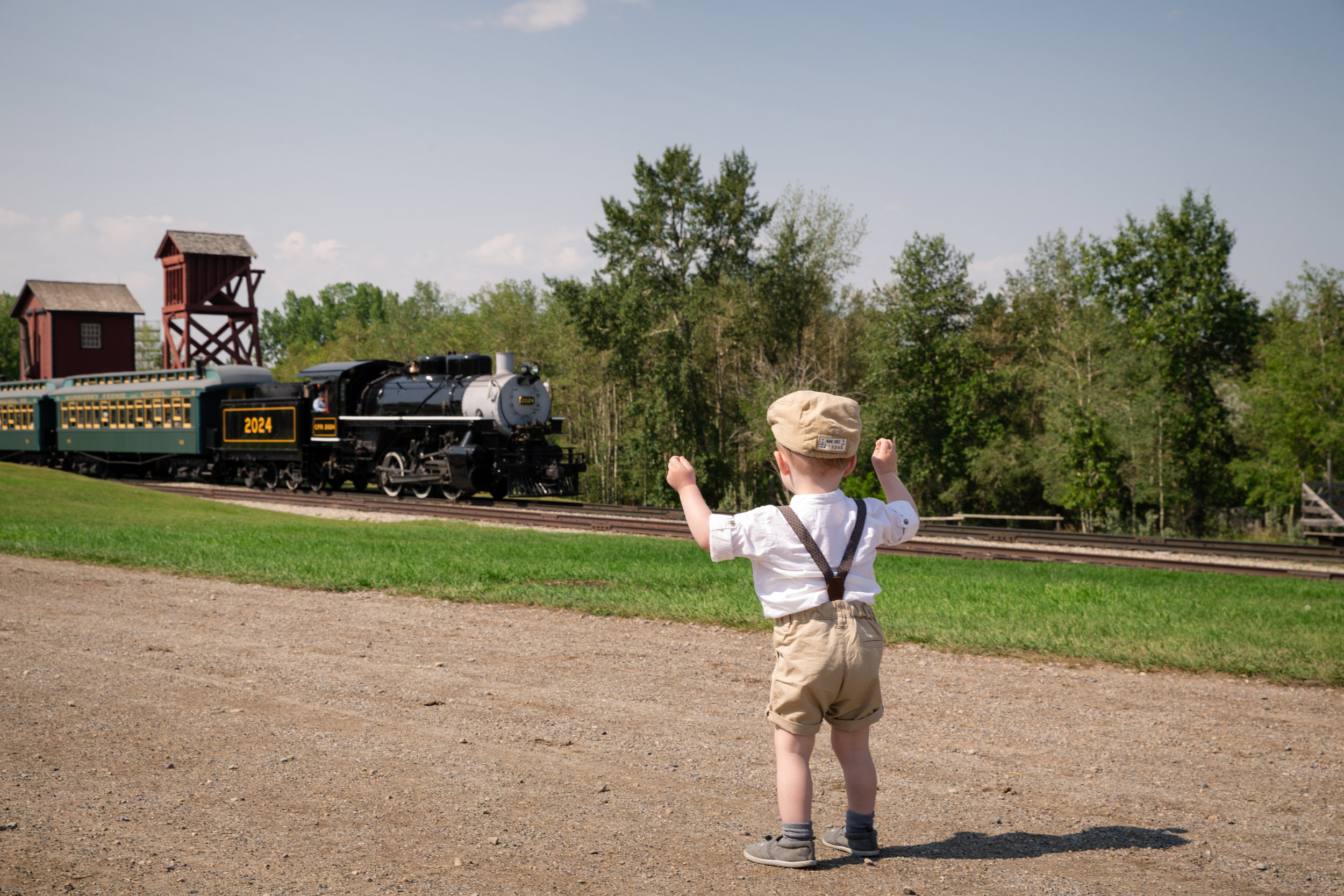 Little boy dressed in the old style clothing looking at the upcoming old style train at the Heritage Park, Calgary. Calgary family photographer. Milashka Photography.