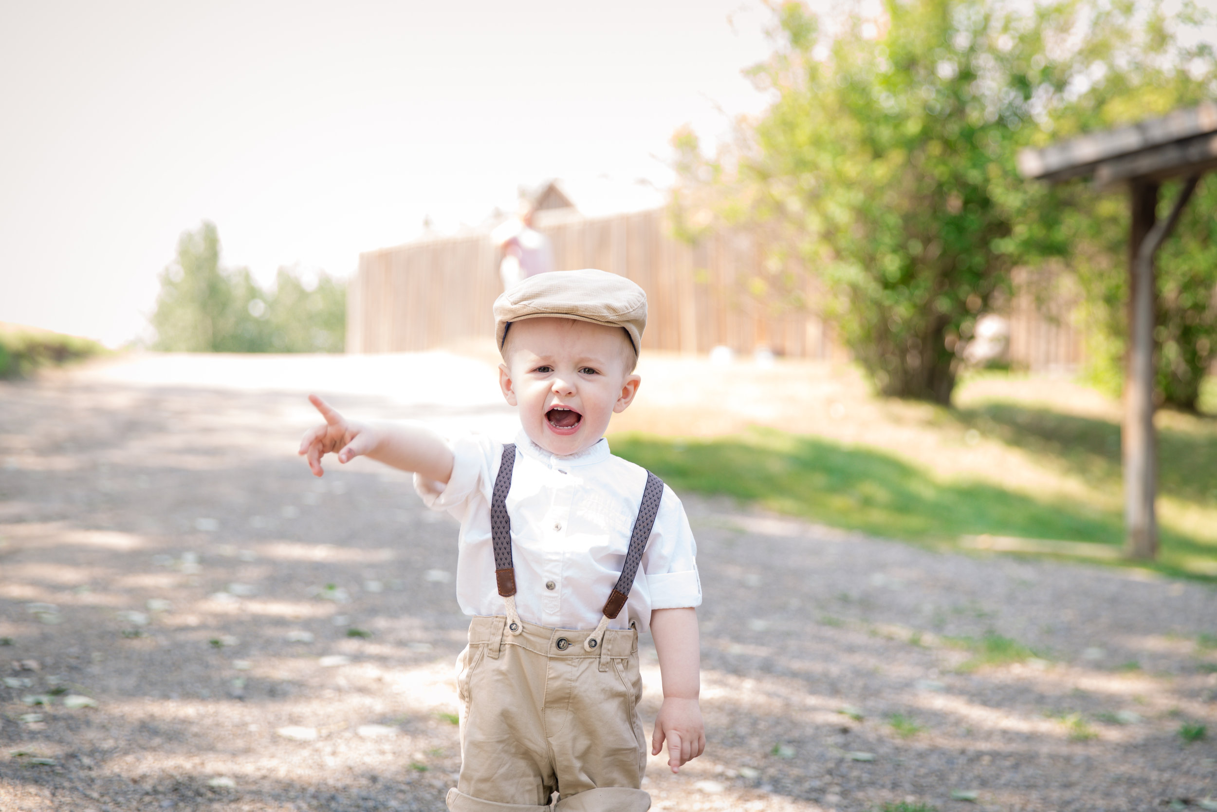 Little boy dressed in old style clothing pointing at something. Calgary Child Photographer. Milashka Photographer.