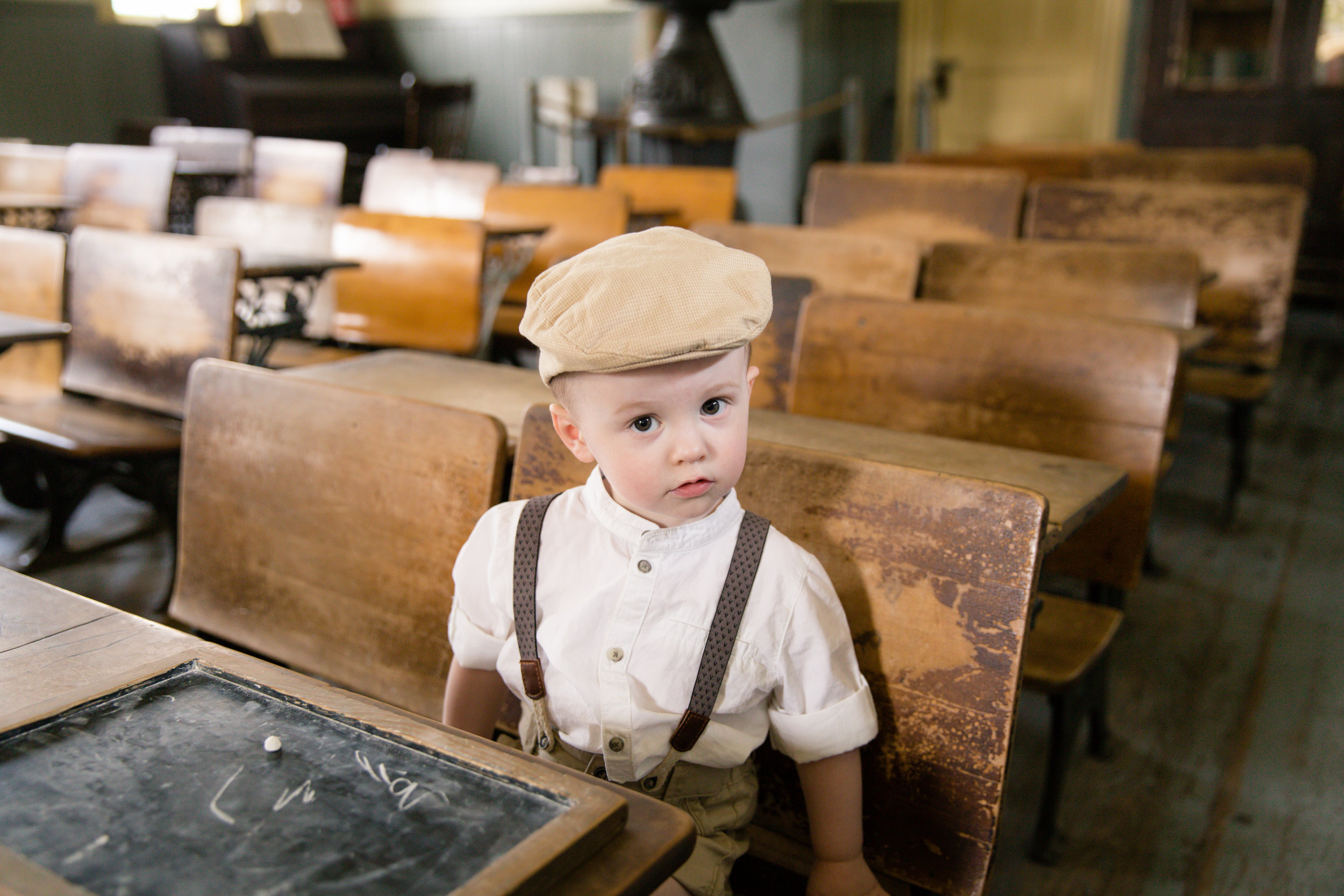 Little boy in an old style school looking curiously at the camera. Calgary photographer. Milashka Photography