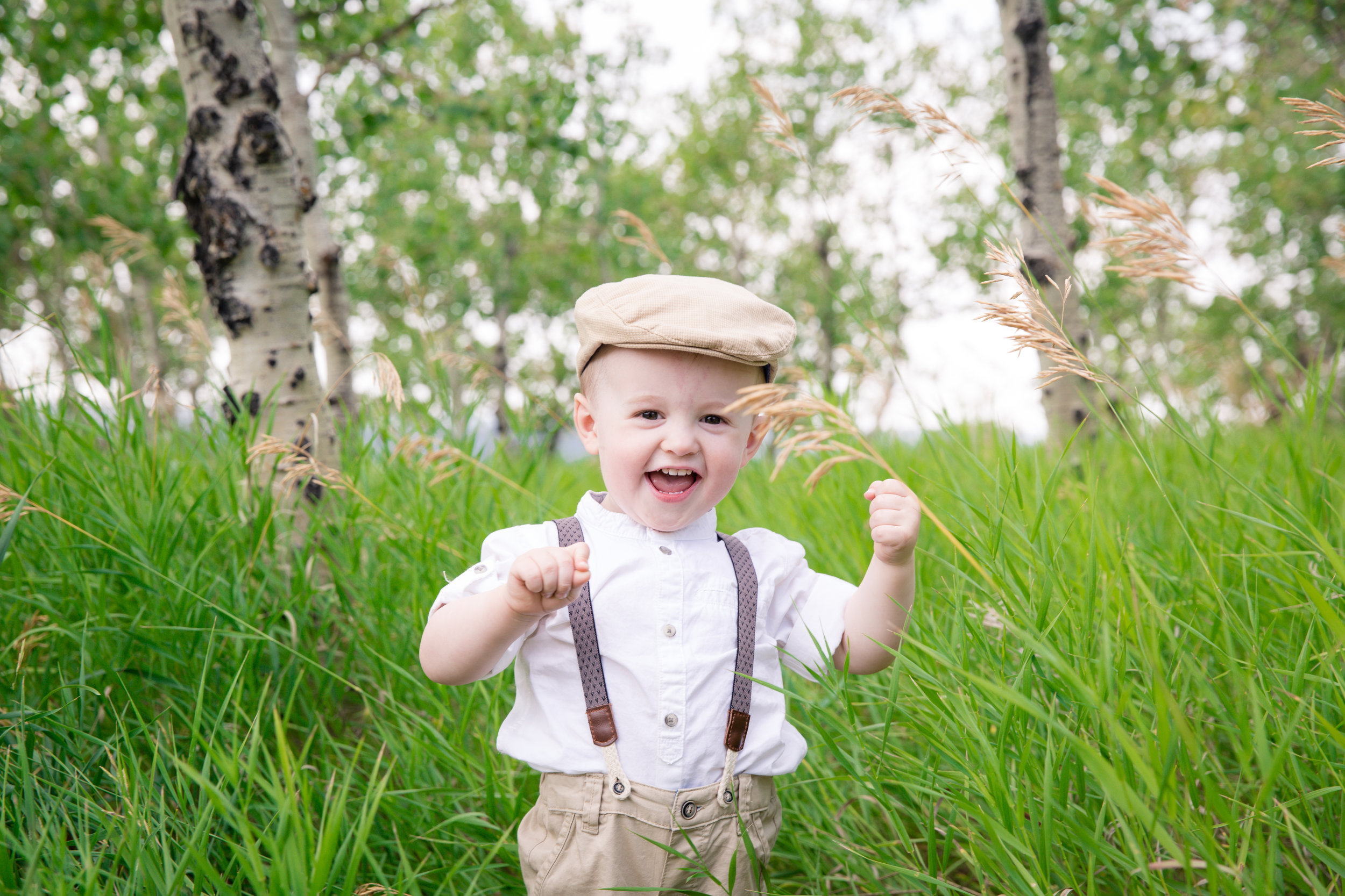 Little boy dressed in an old style clothing standing in tall grass and smiling. Calgary child photographer. Milashka Photography