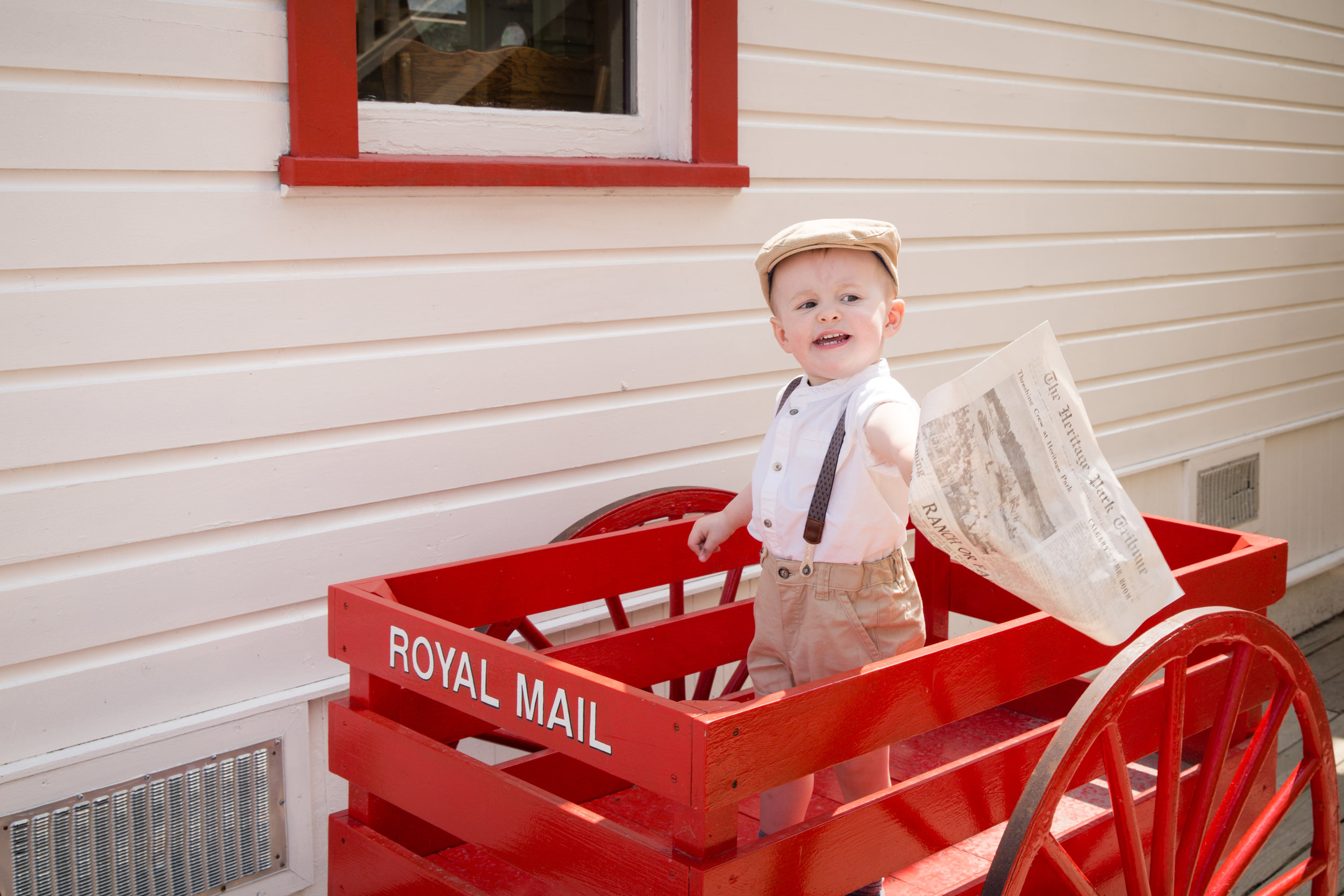 Newspaper anyone? Little cute boy standing in the red Royal Mail wagon at the Heritage Park in Calgary holding old style newspaper. Calgary child and family photographer. Milashka Photography