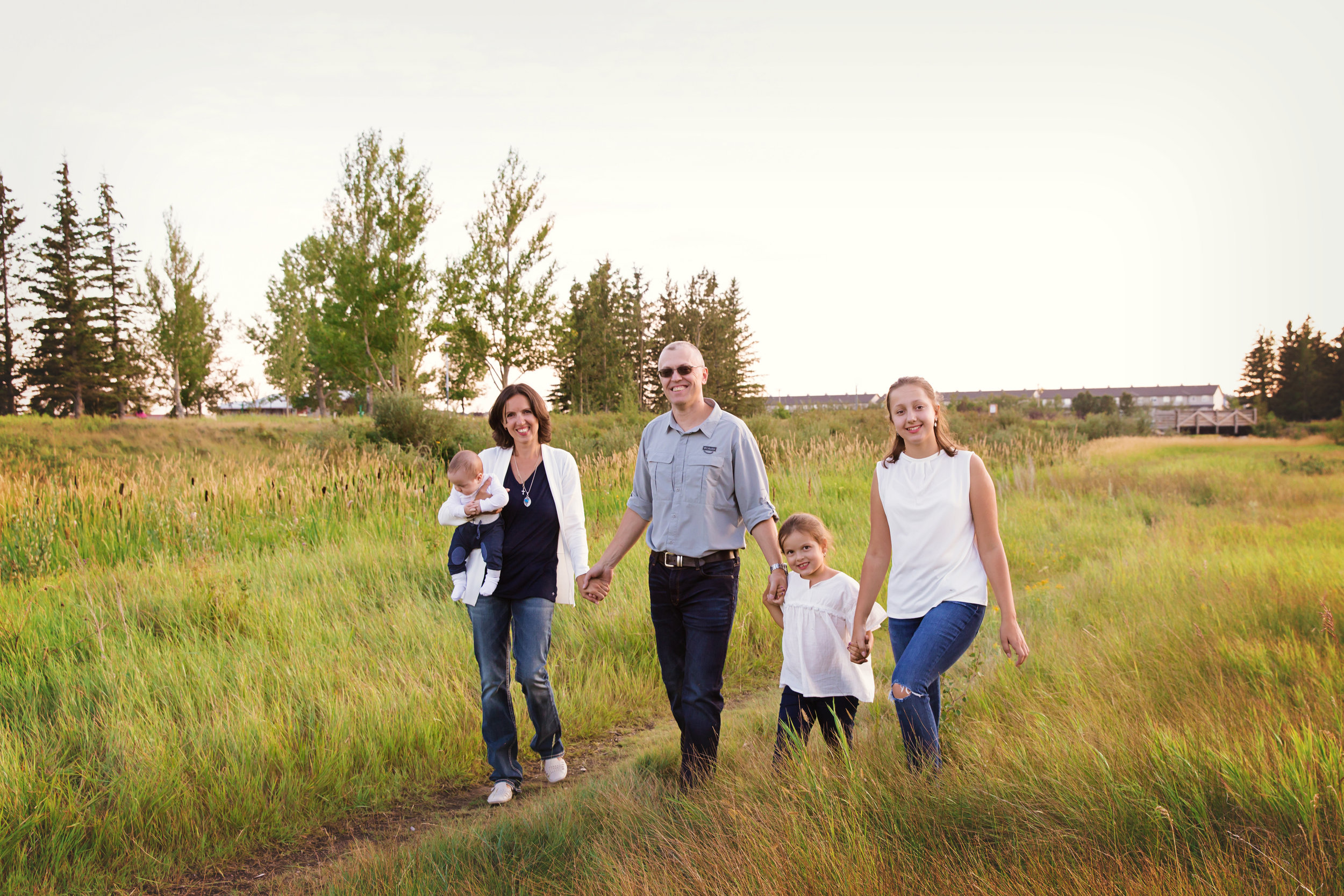 Family of 5 walking and holding hands during a warm summer evening at the Nose Creek Park in Airdrie, Alberta. Airdrie family photographer - Milashka Photography
