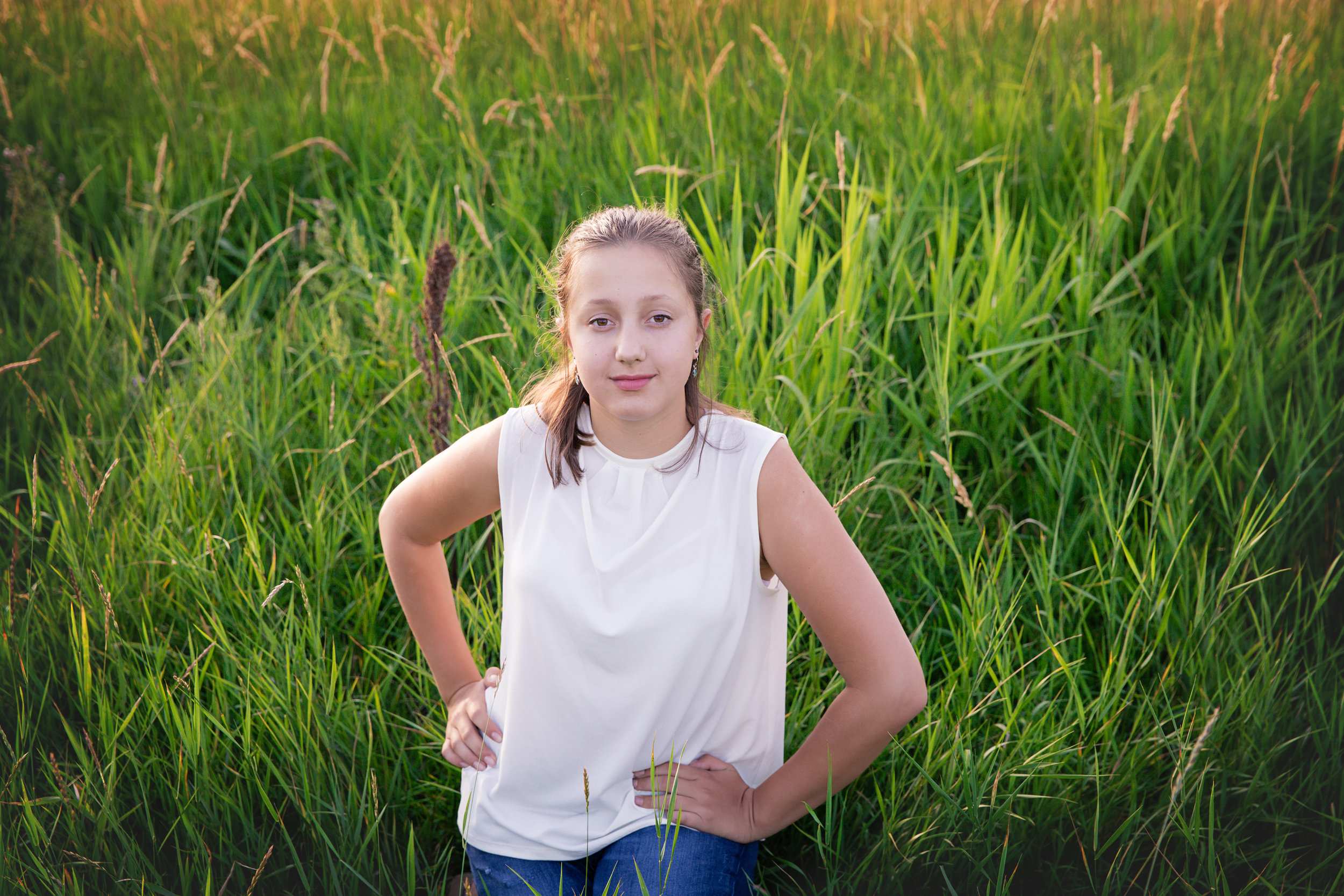 Girl sitting in a tall grass. Airdrie family photographer - Milashka Photography