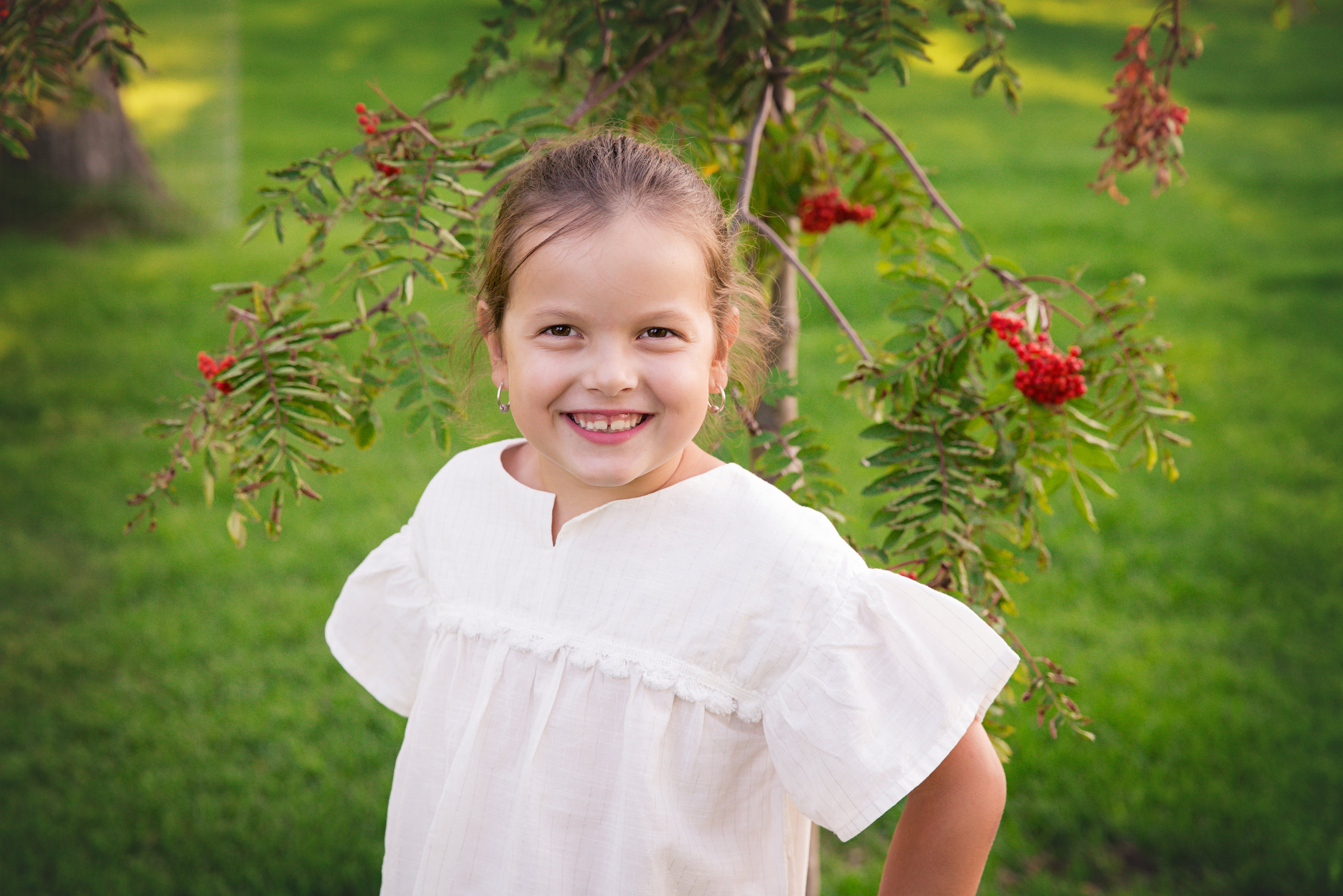 Girl is standing beside a tree with red berries. Airdrie family photographer. Milashka Photography