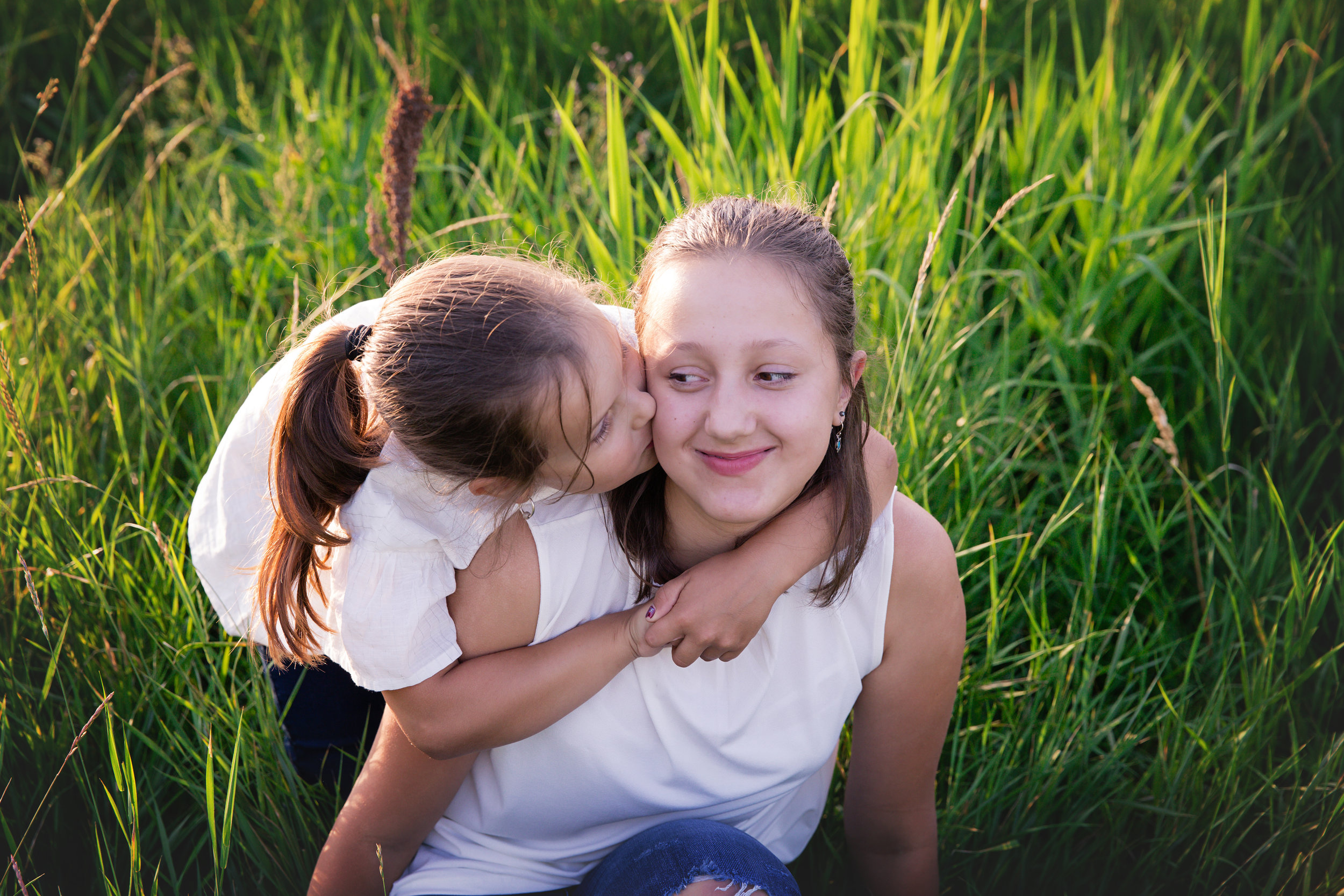 Little sister is giving a kiss to her older sister. Airdrie family photographer. Milashka Photography