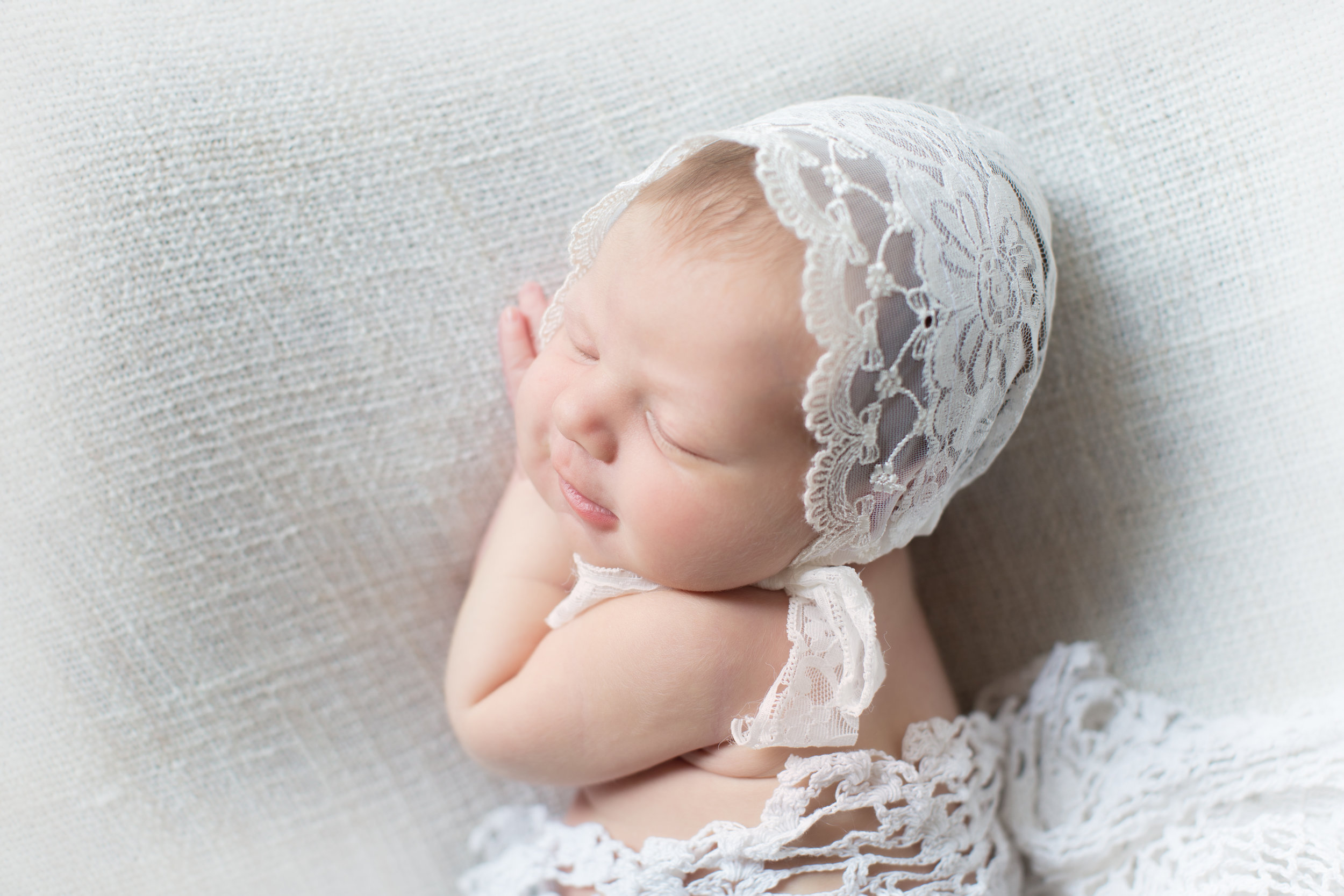 Portrait of a beautiful newborn baby girl in a white bonnet smiling on a beanbag. Calgary newborn photographer. Milashka Photography