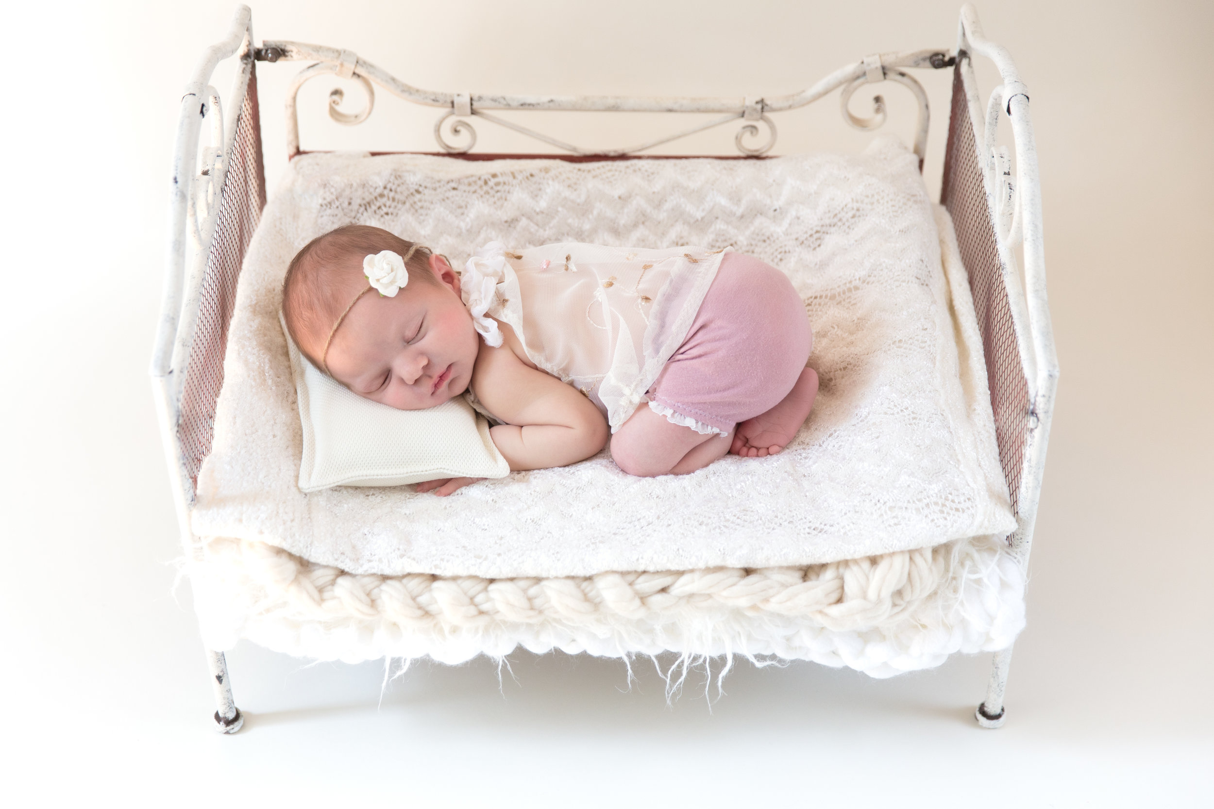 Newborn baby girl lying on an antique bed. Newborn Calgary Photographer - Milashka Photography