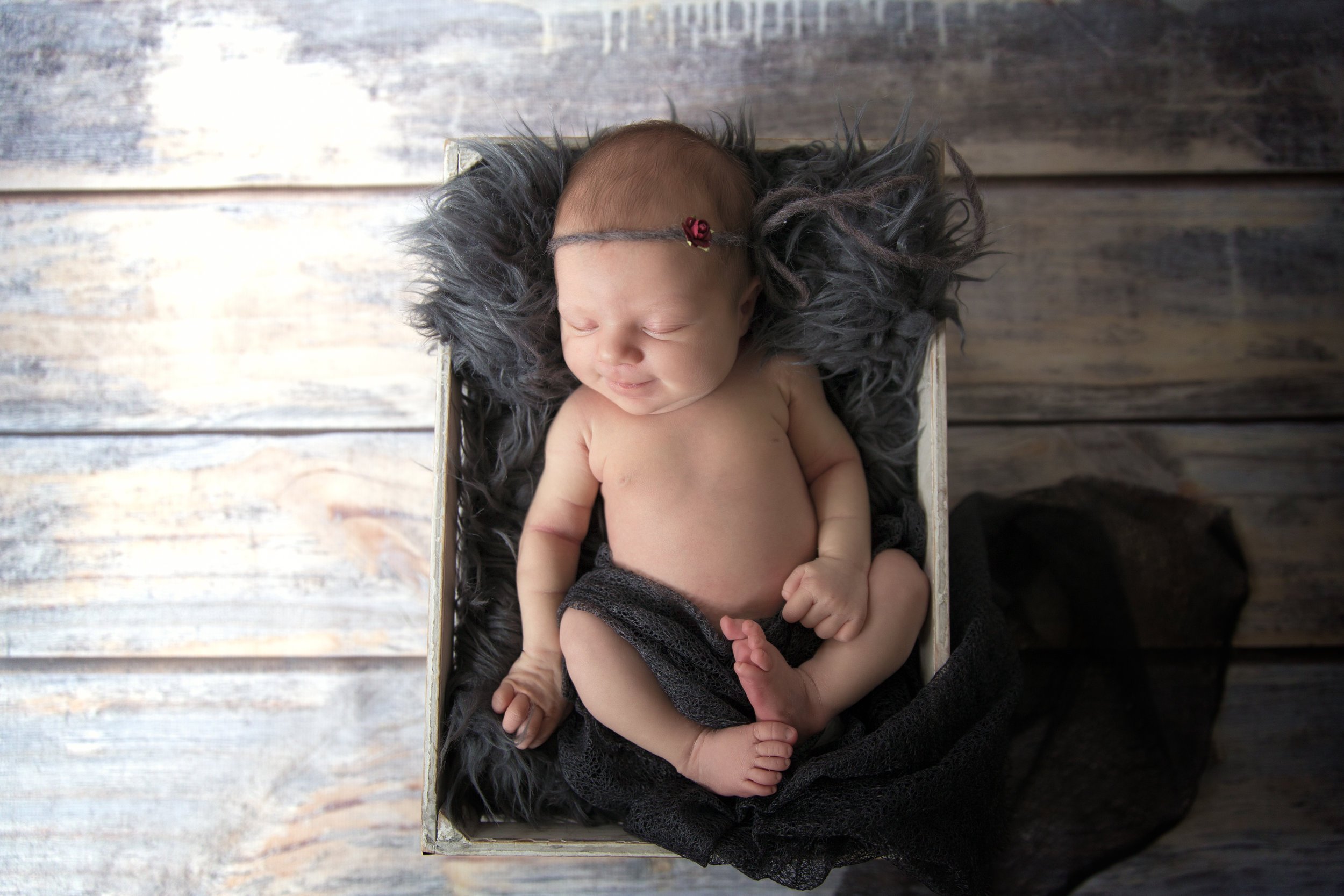 Smiling newborn baby girl in a crate - Calgary newborn photographer - Milashka Photography