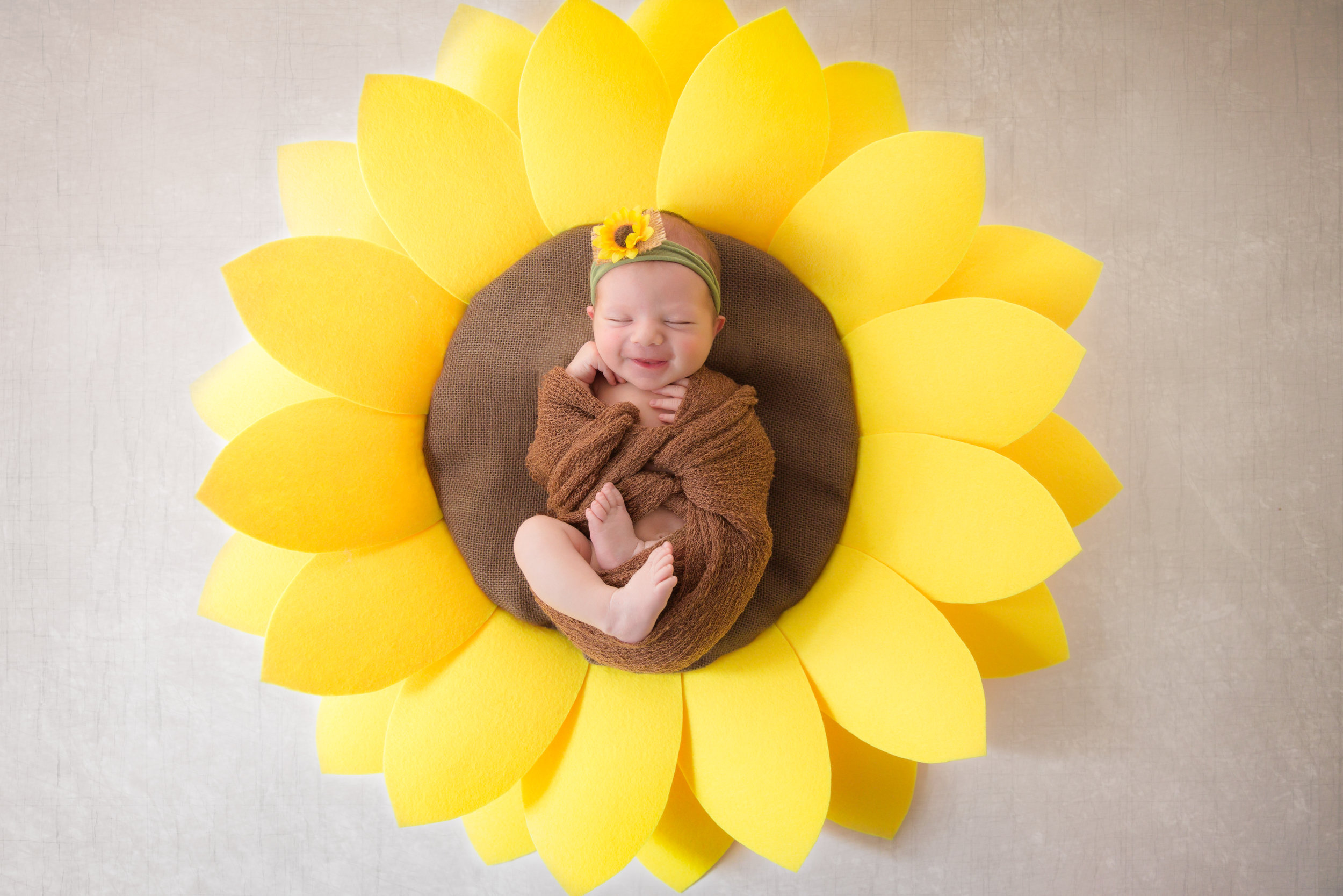 Newborn baby girl lying down in the middle of a sunflower and smiling. Calgary newborn photographer - Milashka Photography