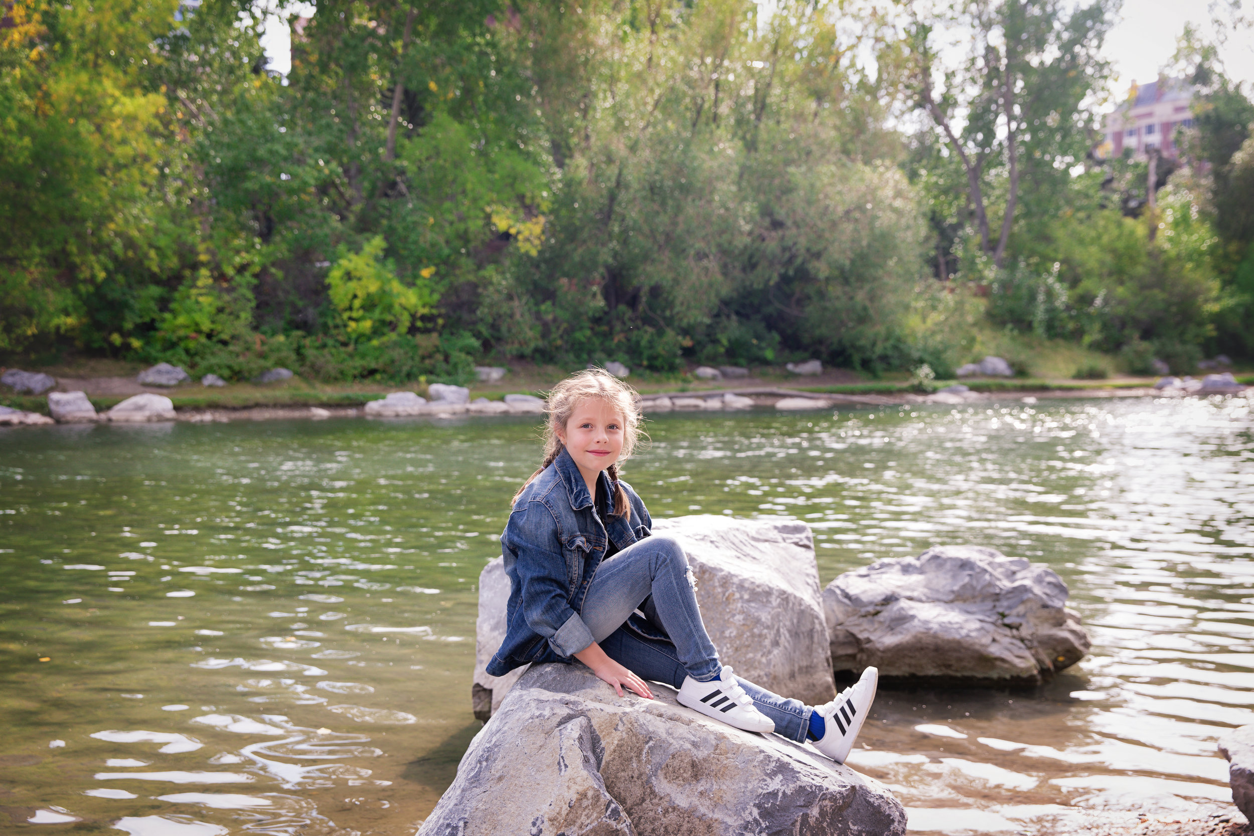 Girl is sitting on a rock and smiling. Calgary family photographer. Milashka Photography.