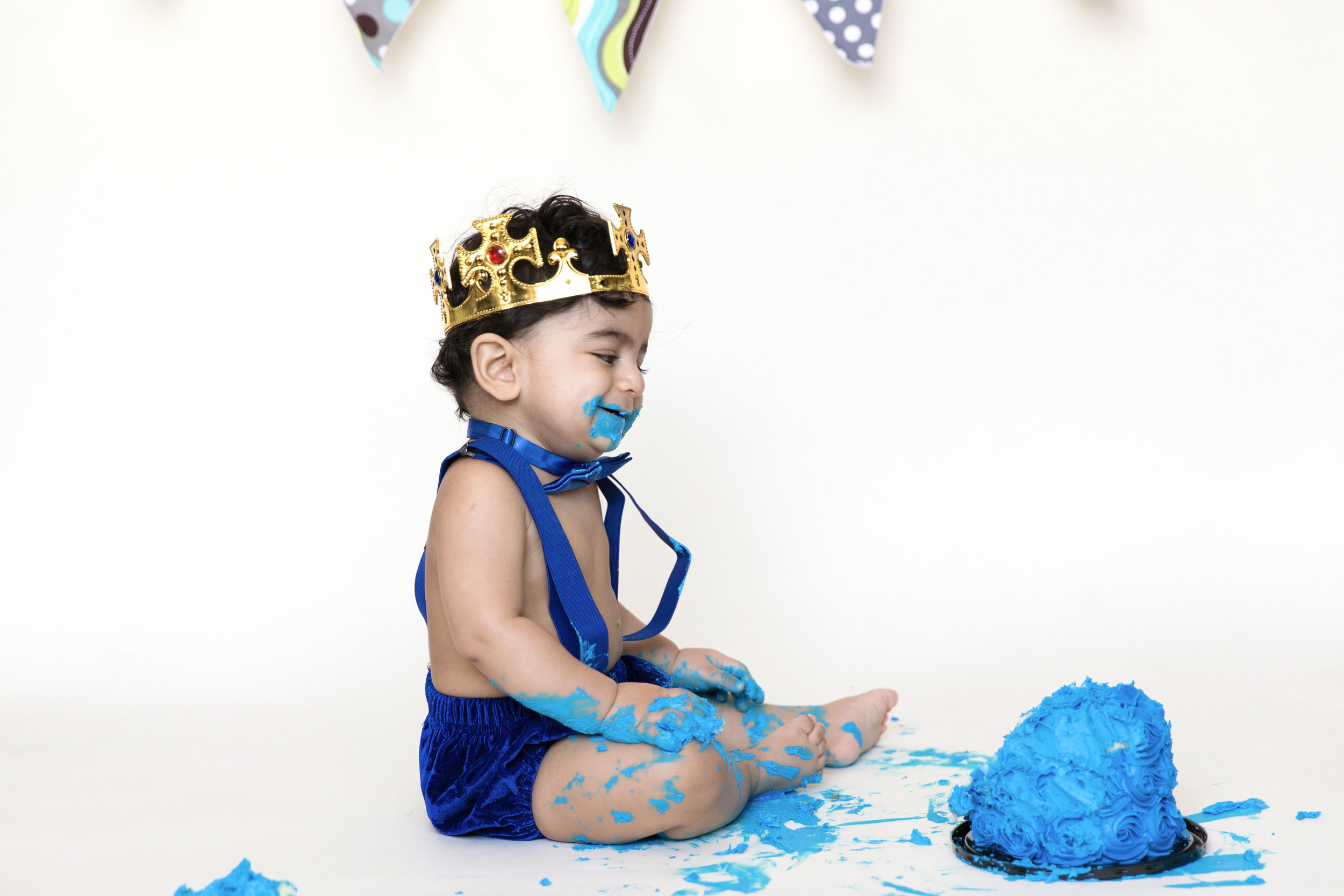 Birthday boy is covered in his cake smiling. Cakesmash photography. Milashka Photography