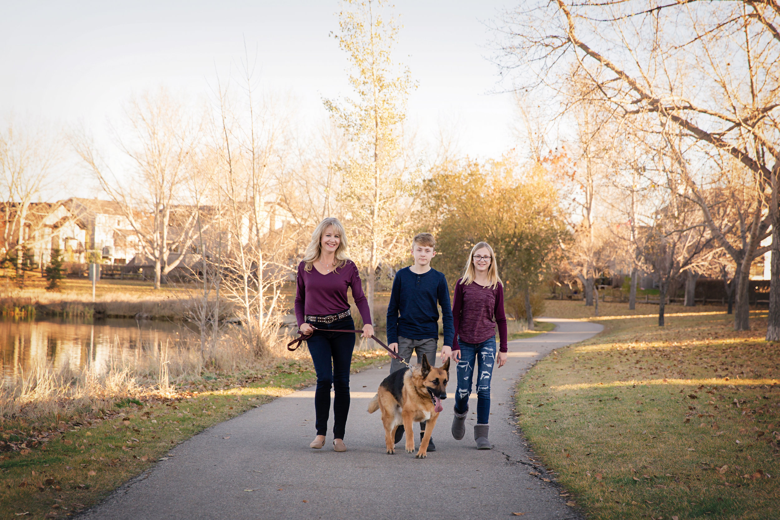 Mom and kids and a dog walking in a park. Fall in Calgary. Calgary family photographer. Milashka photography