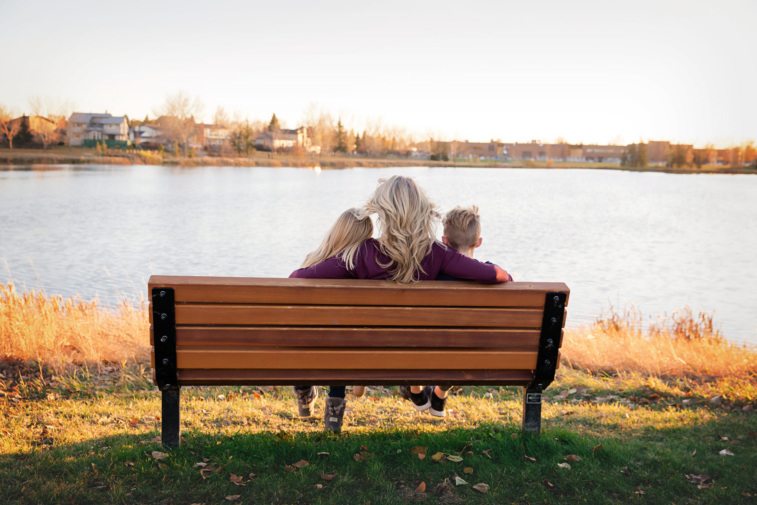 Mom and her 2 kids are sitting on a bench. Calgary family. Milashka Photography