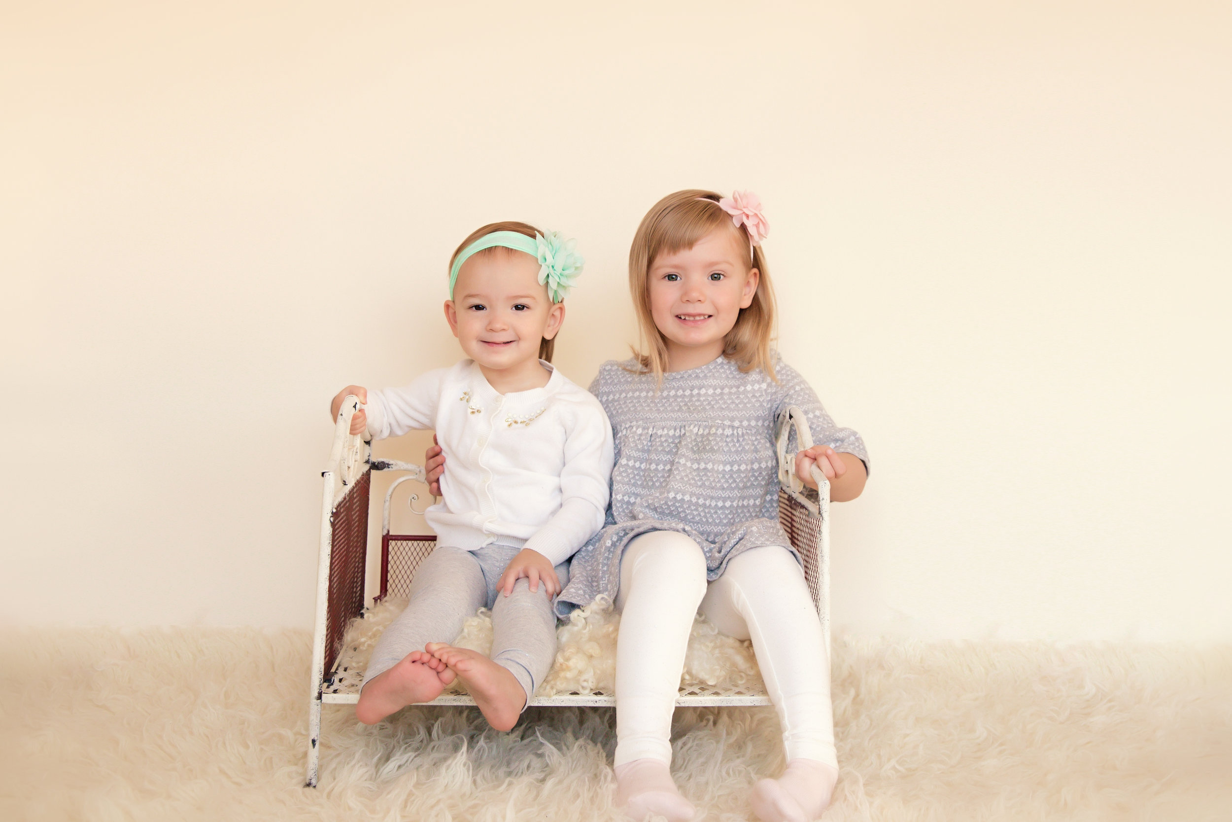 Sisters sitting on a bed and smiling. Calgary children photographer. Milashka Photography