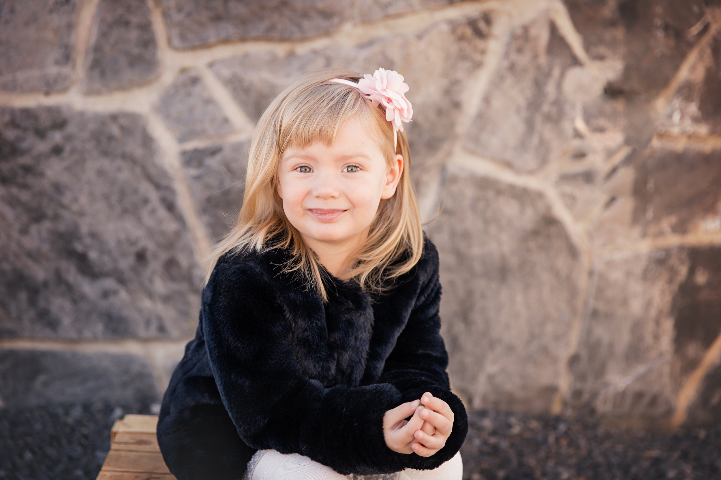 Little girl is smiling and looking into the camera. Calgary photographer. Milashka Photography