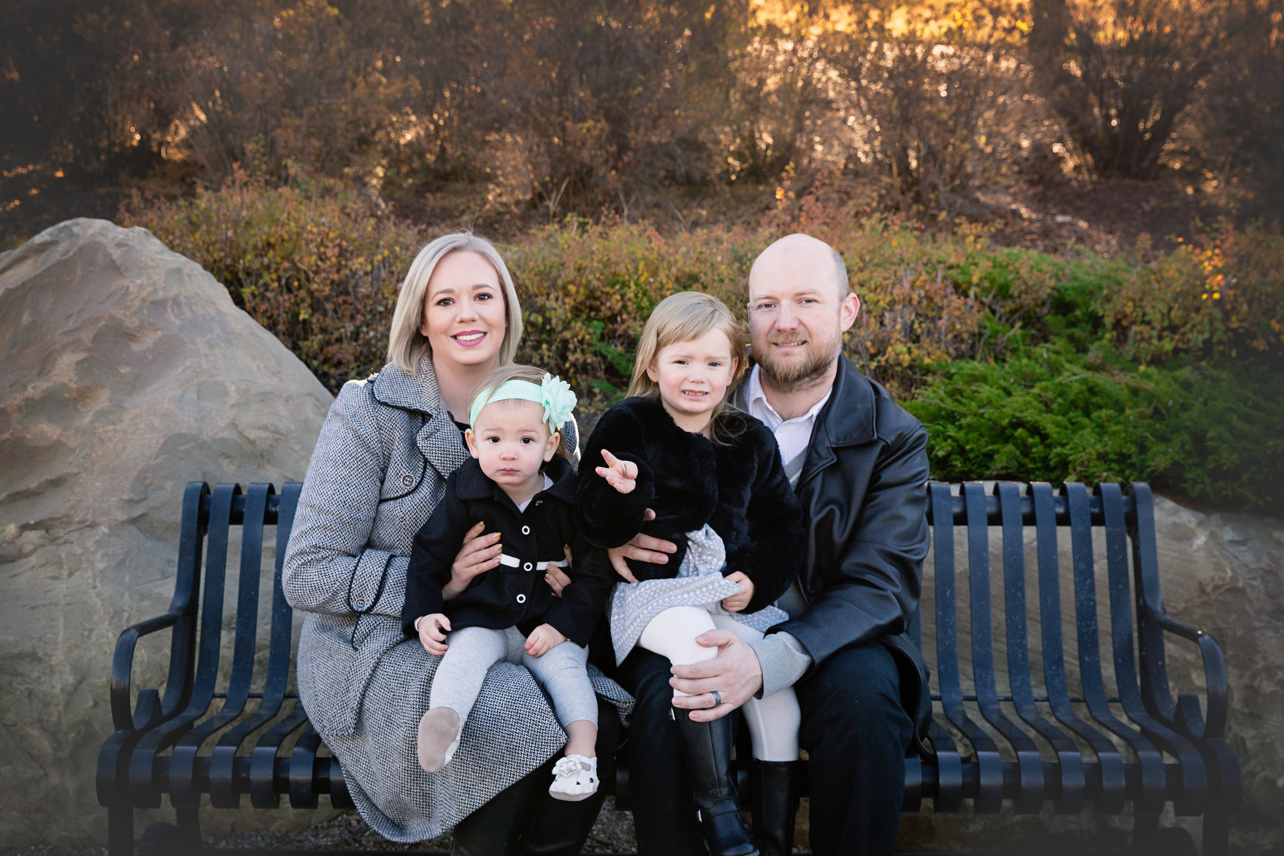 Family of 4 sitting on a bench. Calgary family photographer. Milashka Photography