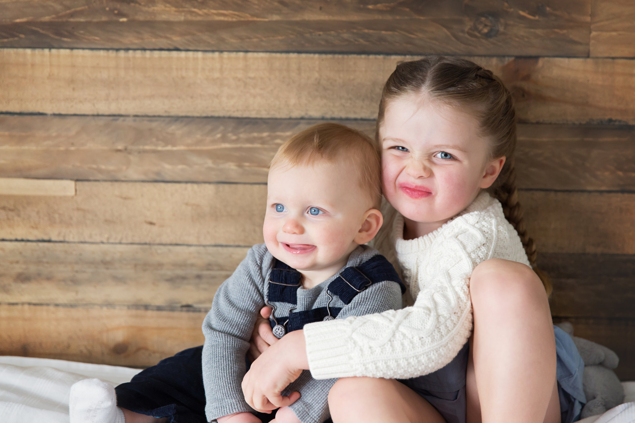 Proud bit sister is holding her baby brother and smiling in this lifestyle inspired photoshoot. Calgary lifestyle family photographer. Milashka Photography