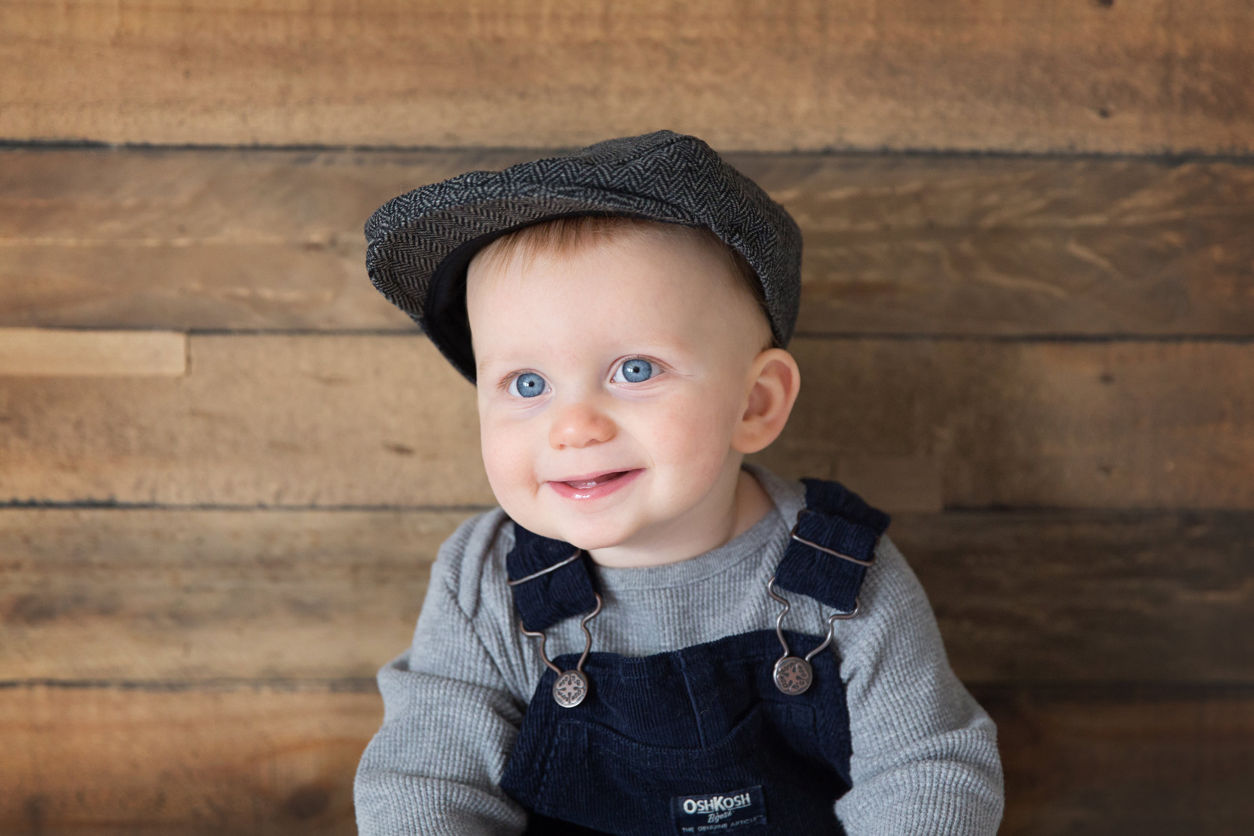 Baby boy is sitting and smiling in a cute hat. Calgary photographer. Milashka photography