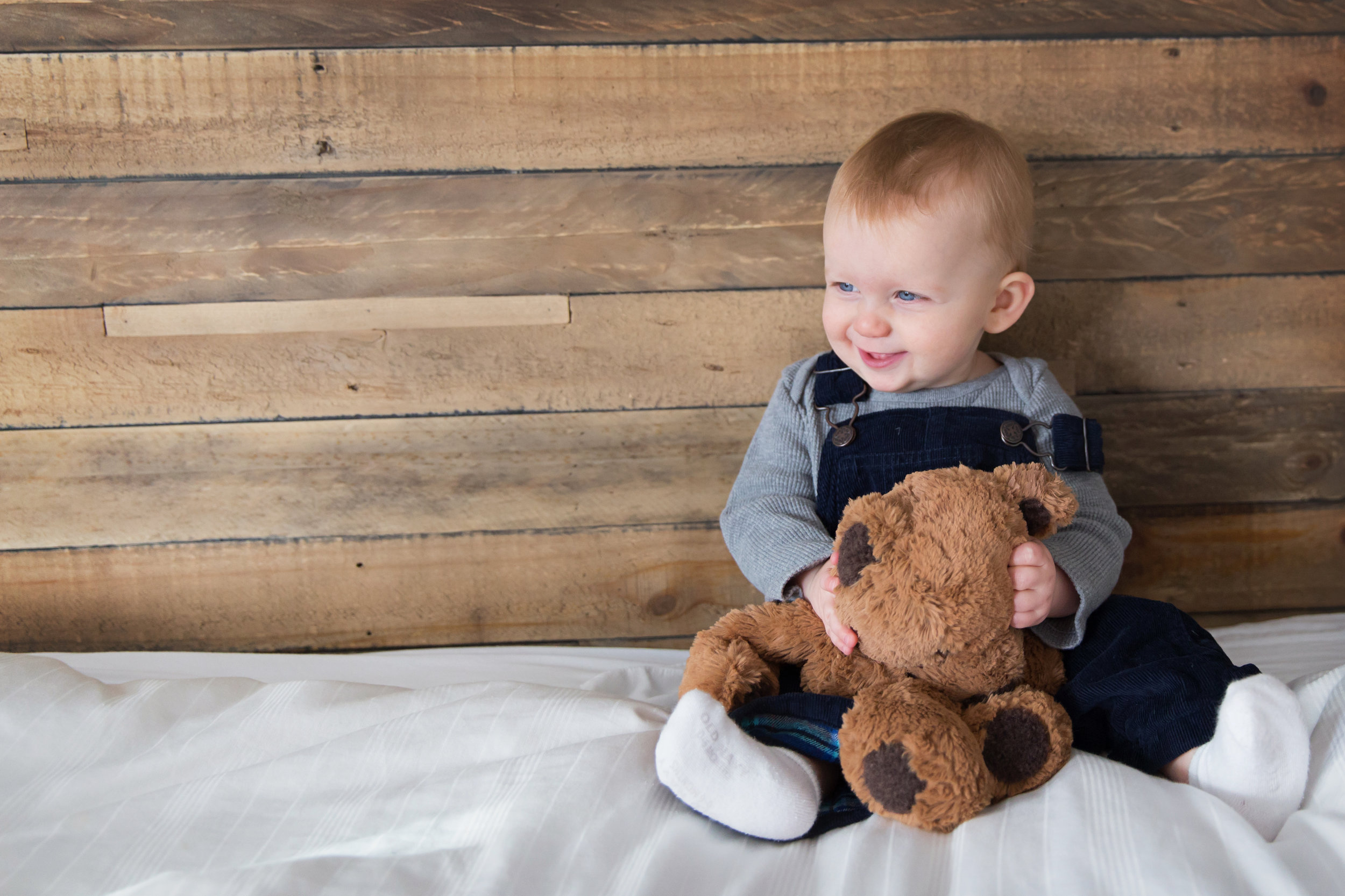 Baby boy sitting on a bed, holding his bear and smiling. Calgary lifestyle photographer. Milashka Photography