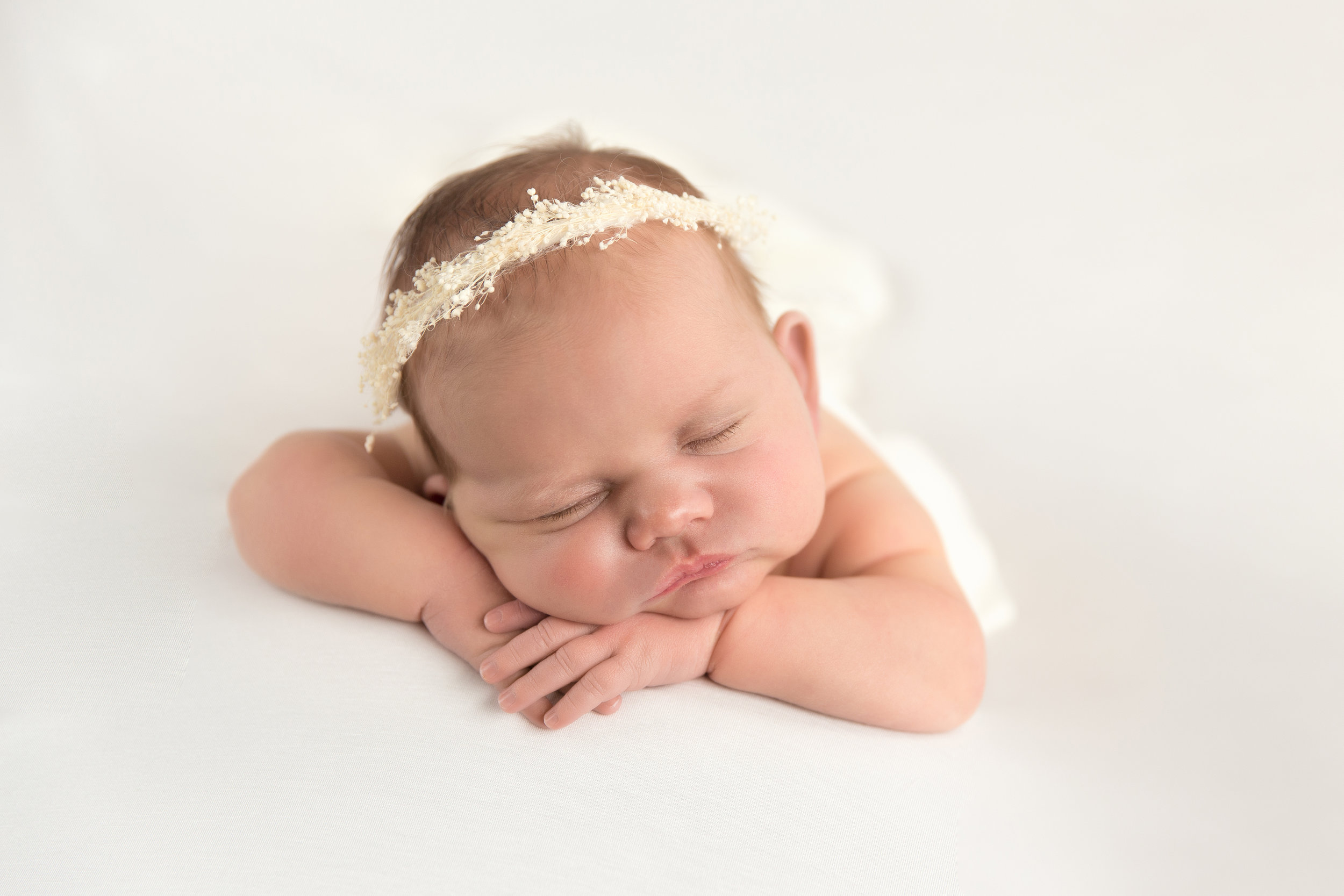 Newborn baby girl on a beanbag with chin on hands pose. Chubby cheeks baby. Calgary and Airdrie Newborn photographer