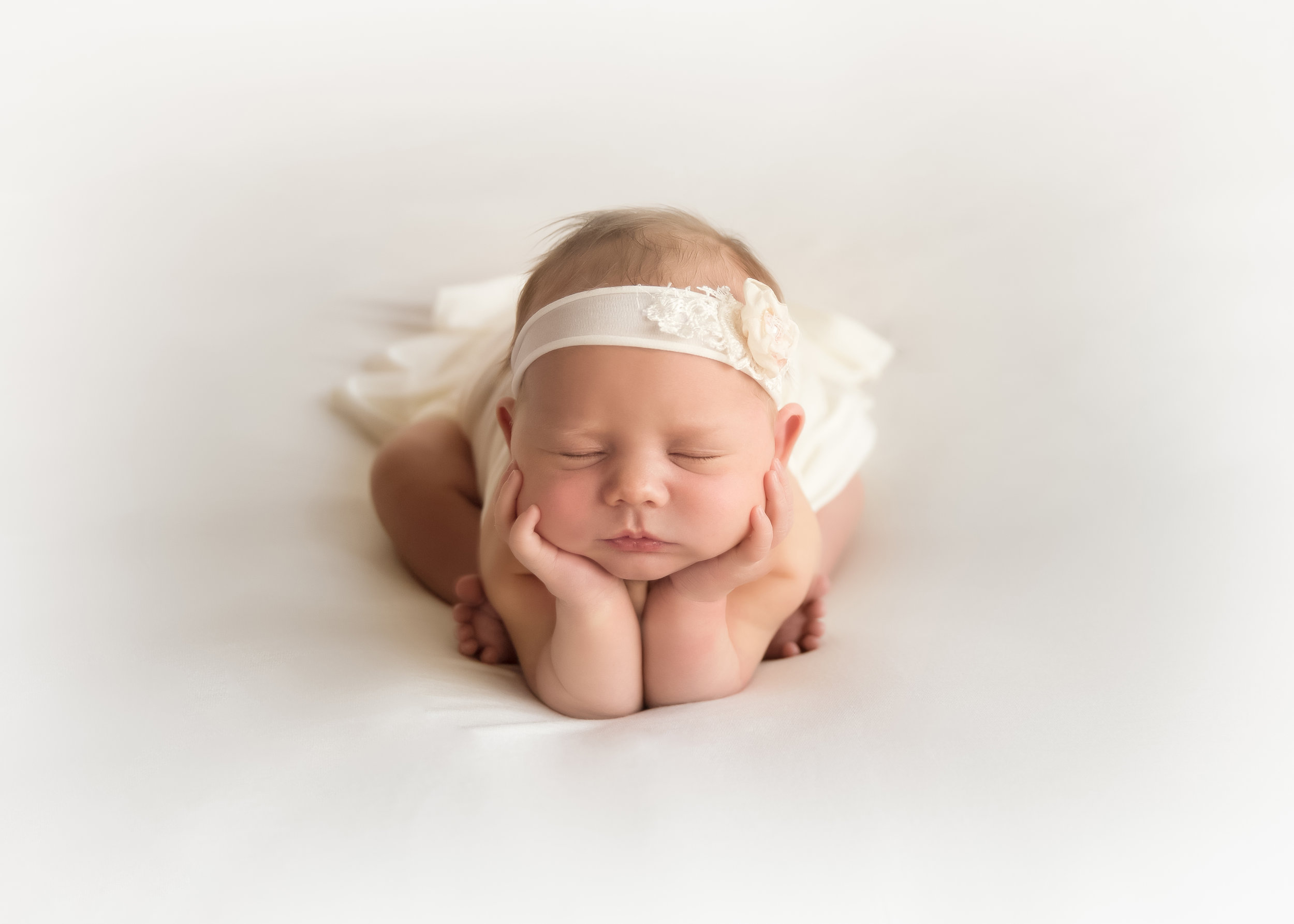 Newborn baby girl in a froggy pose on a beanbag. White backdrop. Newborn photographer in Calgary, Alberta. Milashka Photography
