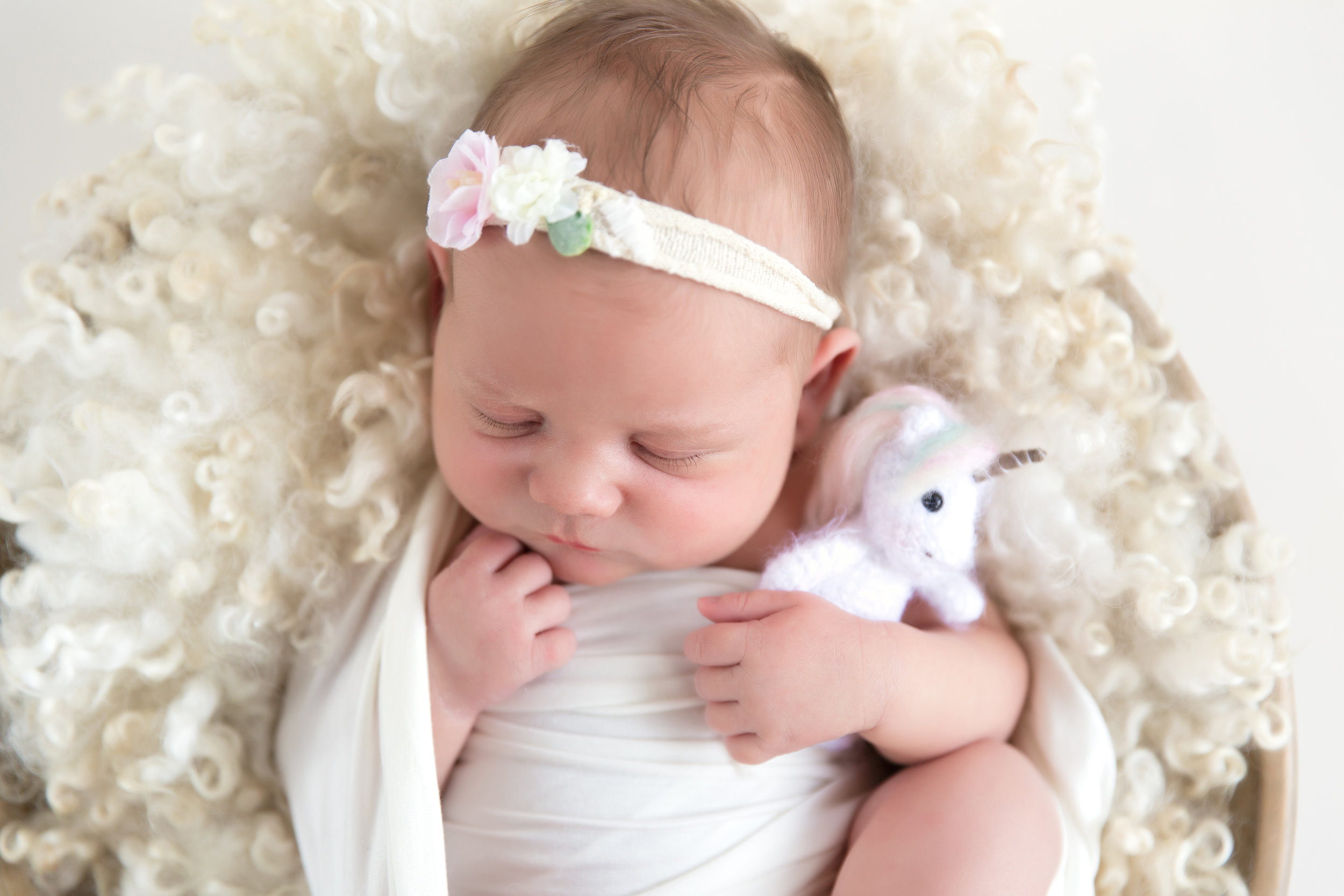 Newborn baby girl with a unicorn plush toy. Airdrie Newborn photographer. Milashka Photography