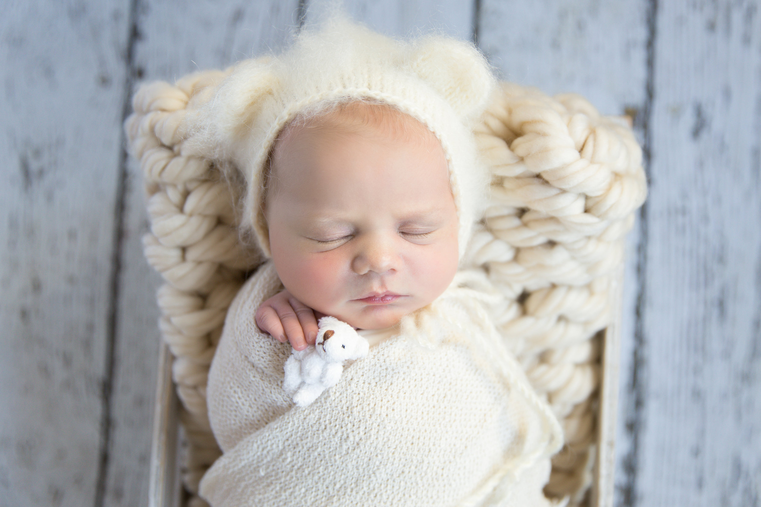 Little baby girl wrapped, wearing bear bonnet and holding a tiny little bear in her hand. Calgary Photographer. Milashka Photography