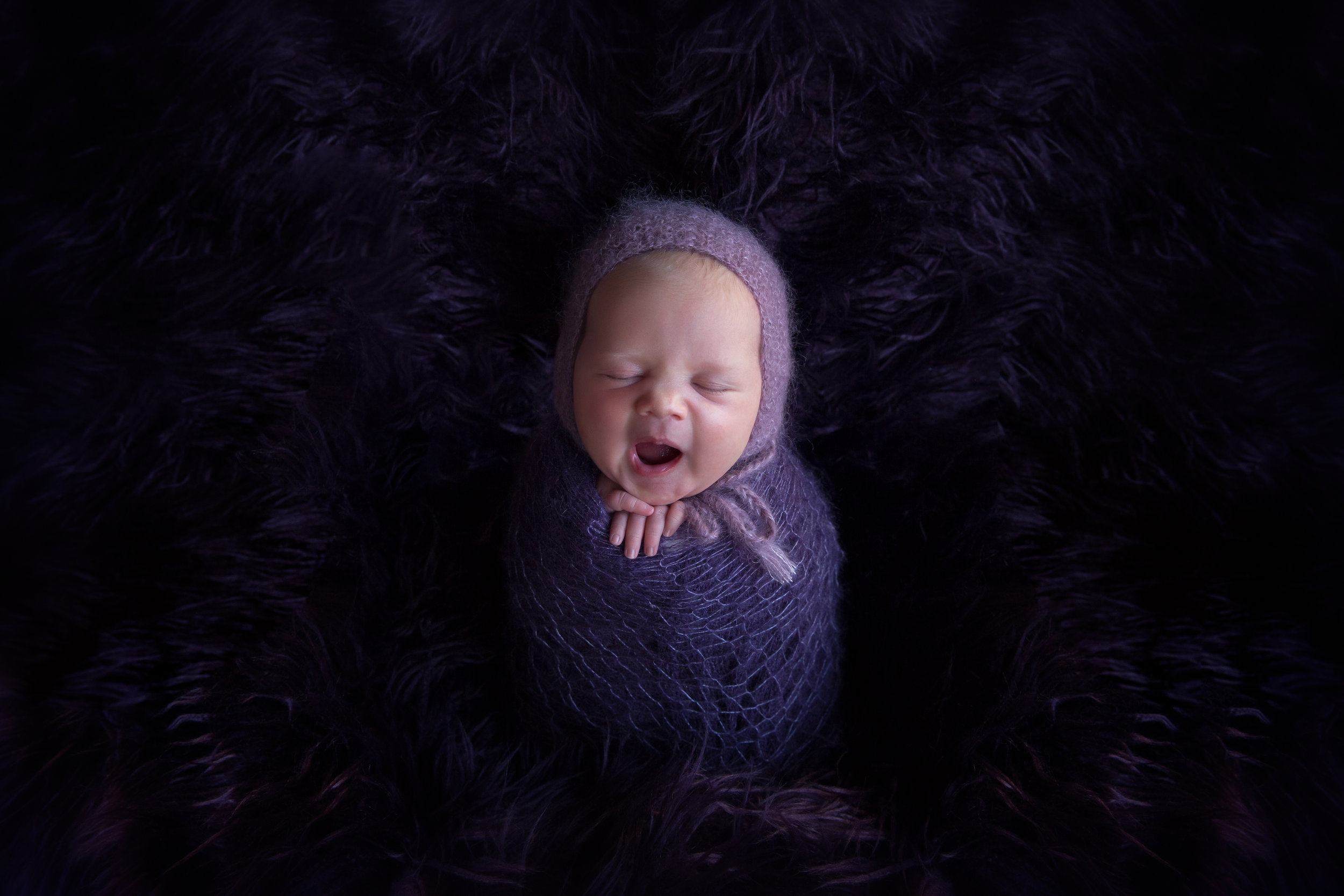 Tired little baby girl is yawning in a potato sack pose on a beanbag. Newborn photography ideas. Calgary Photographer - Milashka Photography