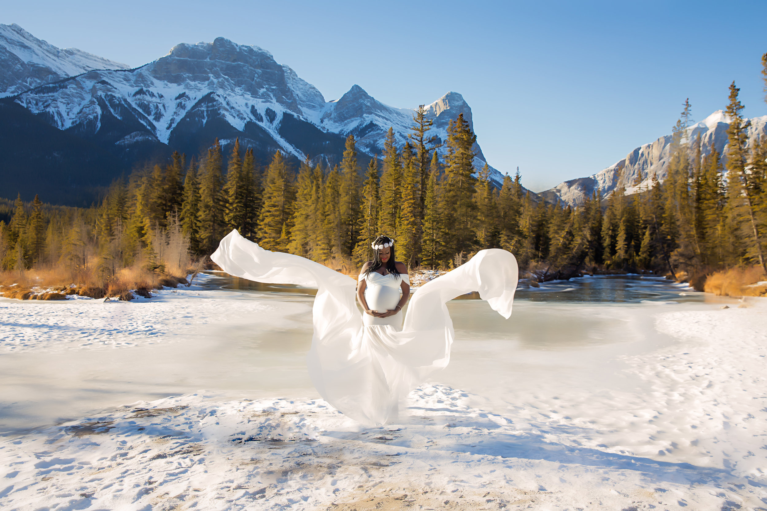 Beautiful mother to be in a white gown on a snow with Rocky Mountains and forest in the background. Calgary Maternity Photographer - Mountain Maternity Session in Alberta - Milashka Photography