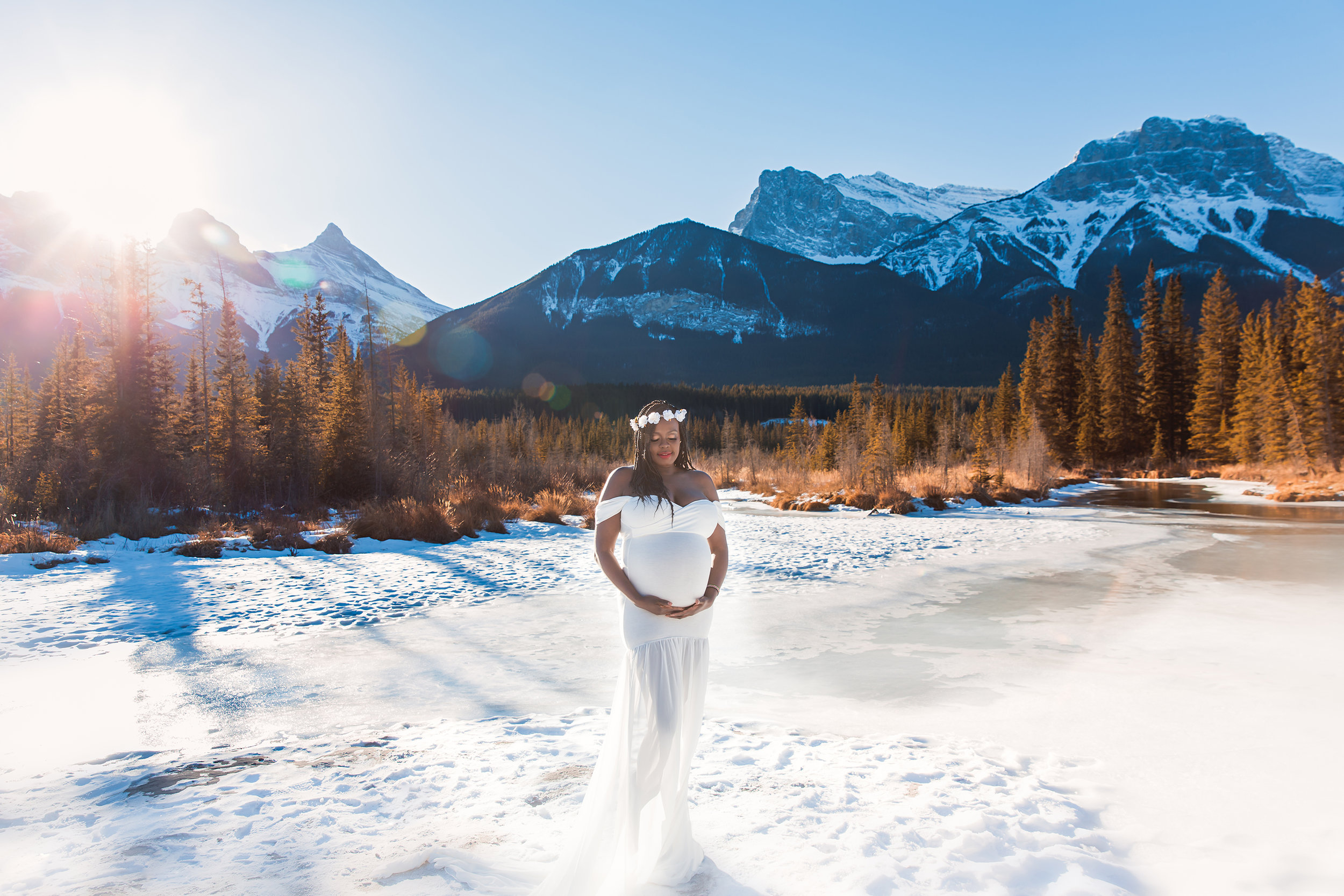 """Blessed"" - the sun is shining upon this pregnant mama, she is standing on a snow in a beautiful white gown with Rocky Mountains and forest in the background. Calgary Maternity Photographer - Mountain Maternity Session in Alberta - Milashka Photography"