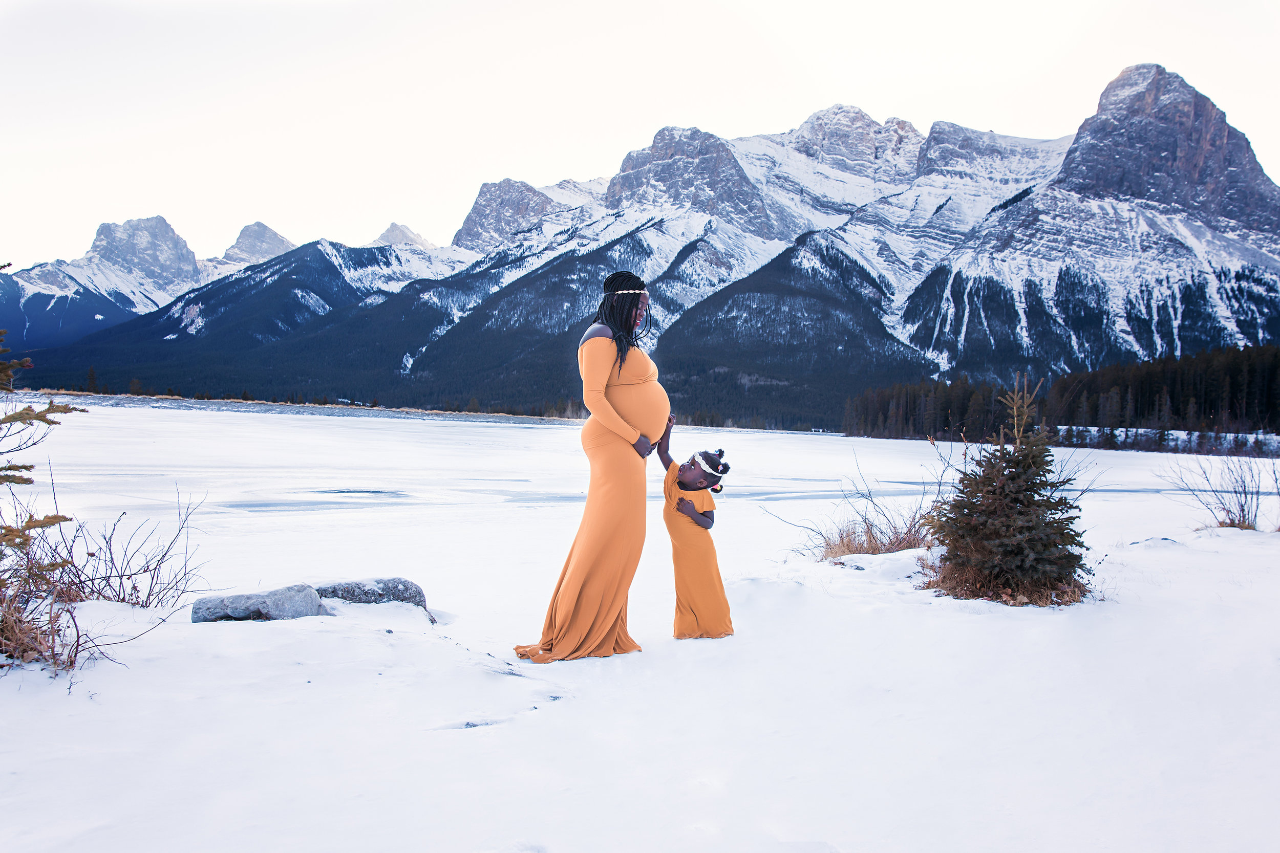 Calgary Maternity Photographer - Mountain Maternity Session in Alberta - Milashka Photography. A beautiful portrait of a mother and daughter both wearing mustard colour gowns standing on a snow in the middle of a winter in beautiful Kananaskis Country in Canmore, Alberta, Canada surrounded by Rocky Mountains.