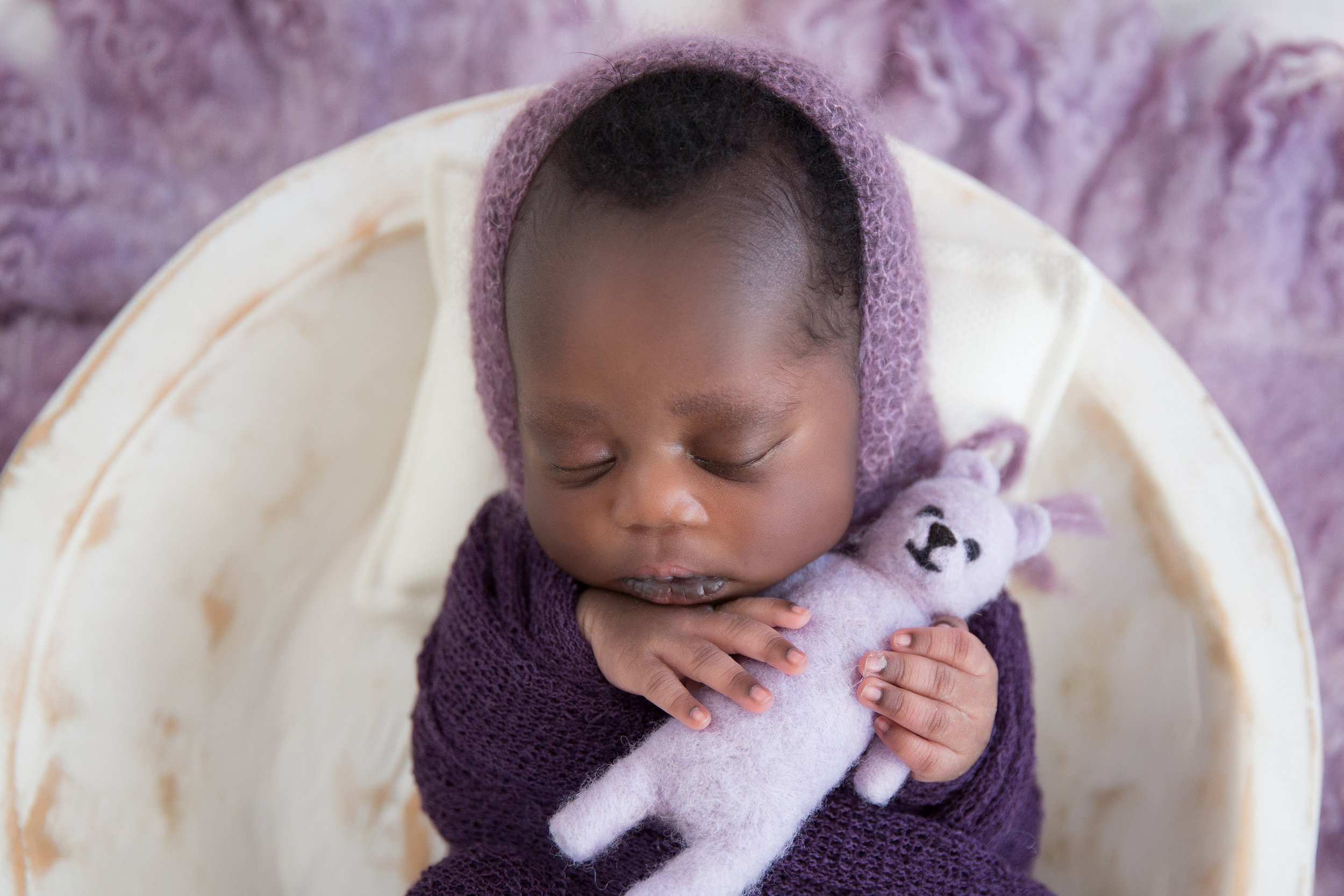 Newborn baby girl is holding a purple bear, wrapped in a purple wrap and wearing a purple hat, lying in a white wooden bowl. Newborn Photoshoot ideas. Calgary and Airdrie Newborn photographer