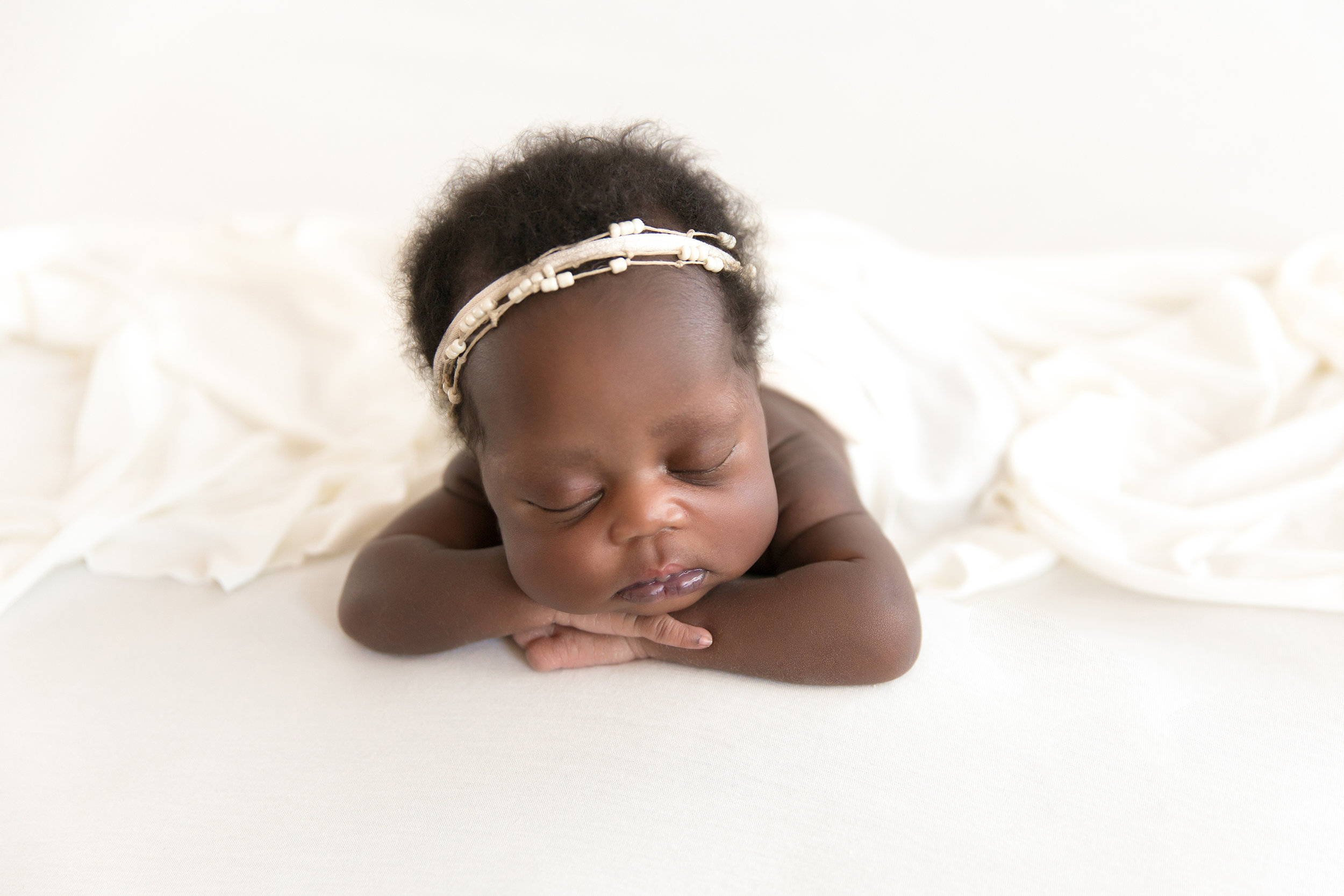 Chin on hands pose. Newborn Photoshoot on a beanbag. Beautiful newborn baby girl is lying on a beanbag. White wrap and white backdrop and white headbands. Newborn Photoshoot idea. Calgary Newbon photographer - Milashka Photography