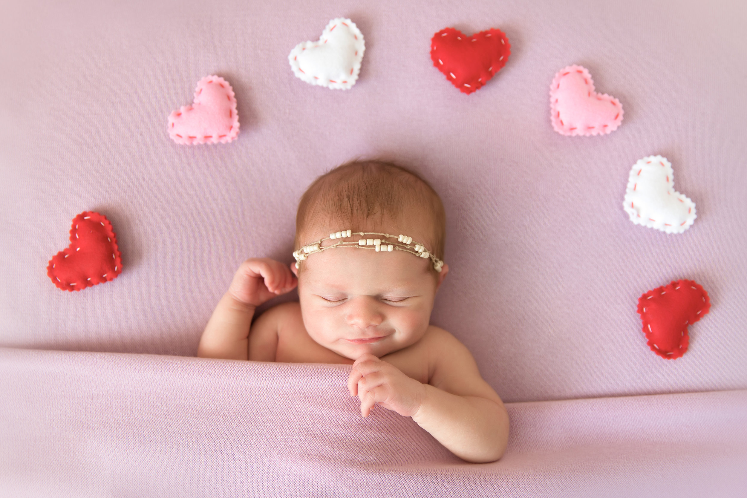 Newborn Photoshoot ideas. Newborn baby girl on a beanbag smiling and surrounded by little hearts. Calgary Newborn photographer. Milashka Photography