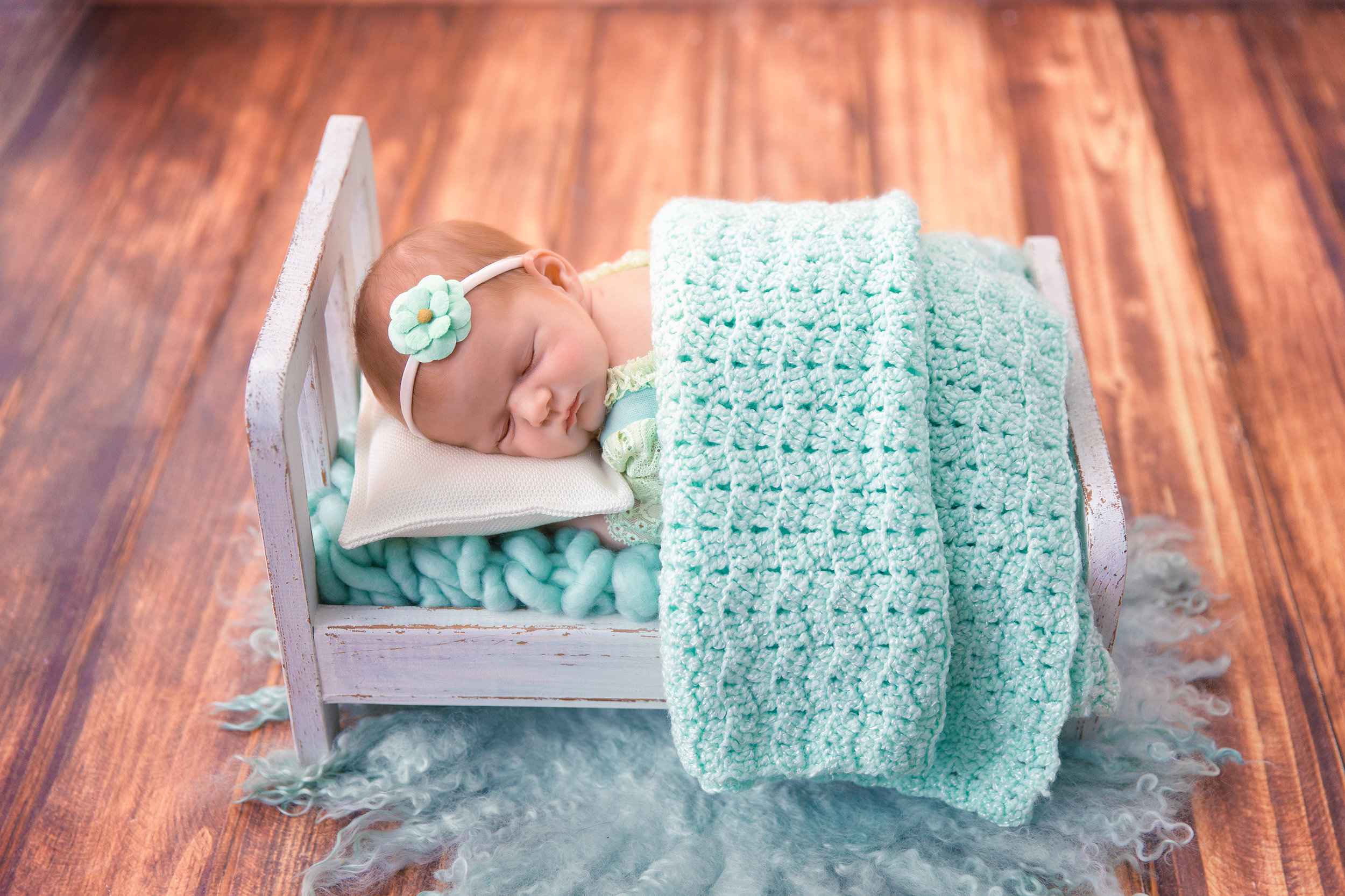 Sleeping beauty. Newborn Photoshoot. Newborn baby girl is sleeping soundly on a little barn bed wearing mint colour outfit. Calgary Newborn photographer - Milashka Photography