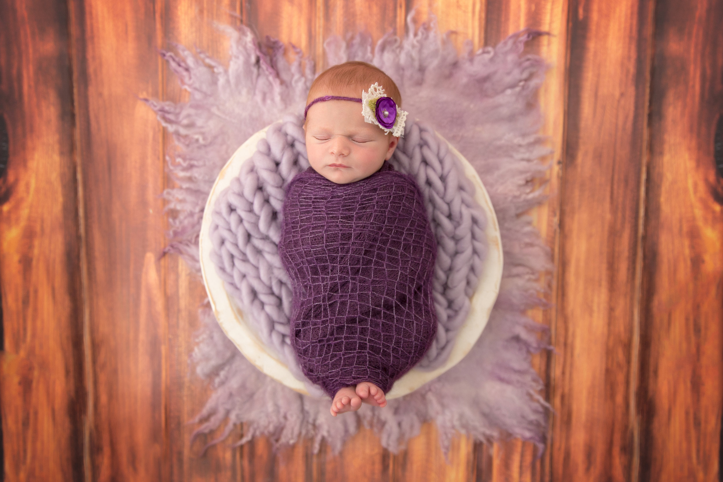 Baby girl wrapped in a purple wrap with her little toes showing lying in a white wooden bowl. Calgary Photographer - Milashka Photography - Newborn photography - Newborn Photoshoot inspiration ideas.
